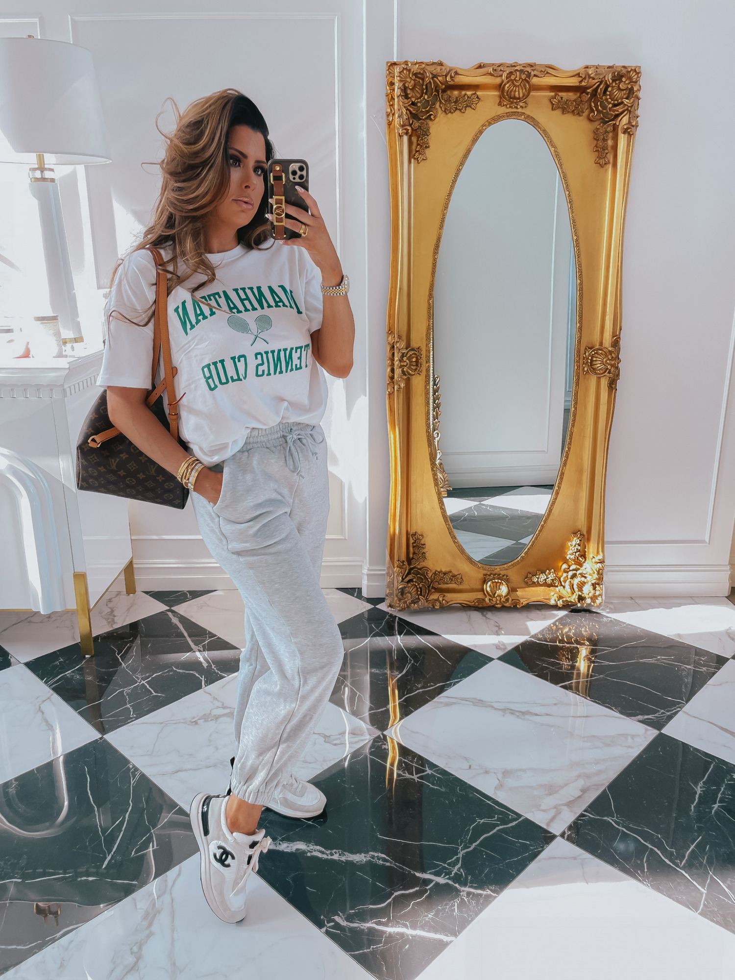 Emily-ann-gemma-abercrombie-tee-shirt-sweatpants-outfit-ltk-day-sale | LTK Sales by popular US fashion blog, The Sweetest Thing: image of Emily Gemma wearing a Manhattan Tennis Club shirt, grey sweatpants and sneakers.