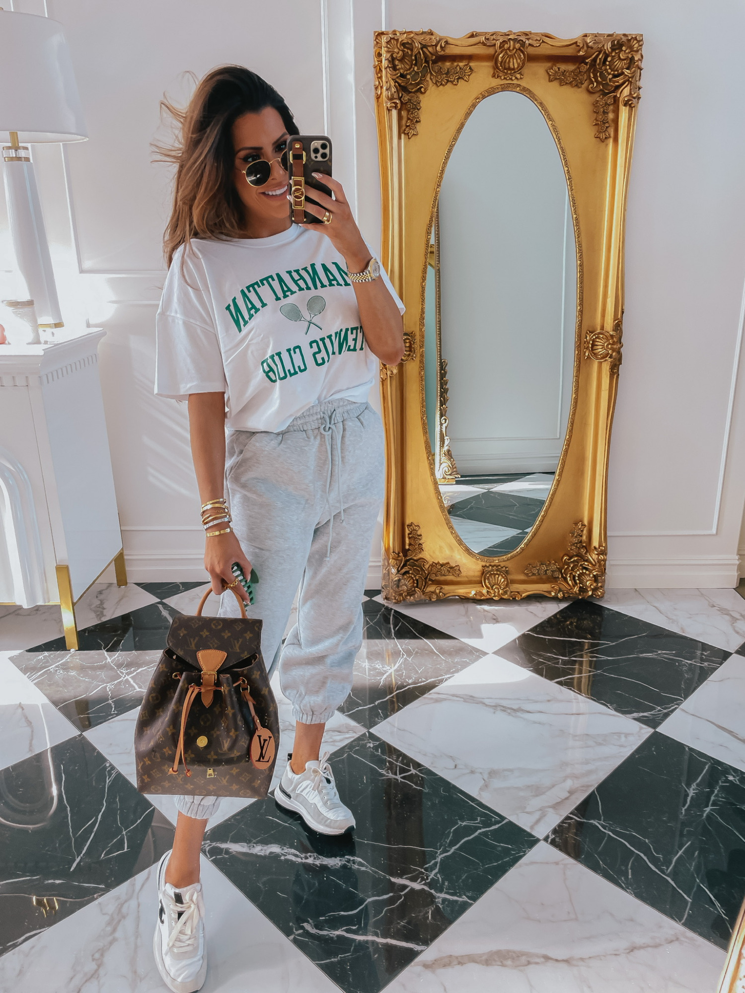 Emily-ann-gemma-abercrombie-tee-shirt-sweatpants-outfit-ltk-day-sale   LTK Sales by popular US fashion blog, The Sweetest Thing: image of Emily Gemma wearing a Manhattan Tennis Club shirt, grey sweatpants and sneakers.