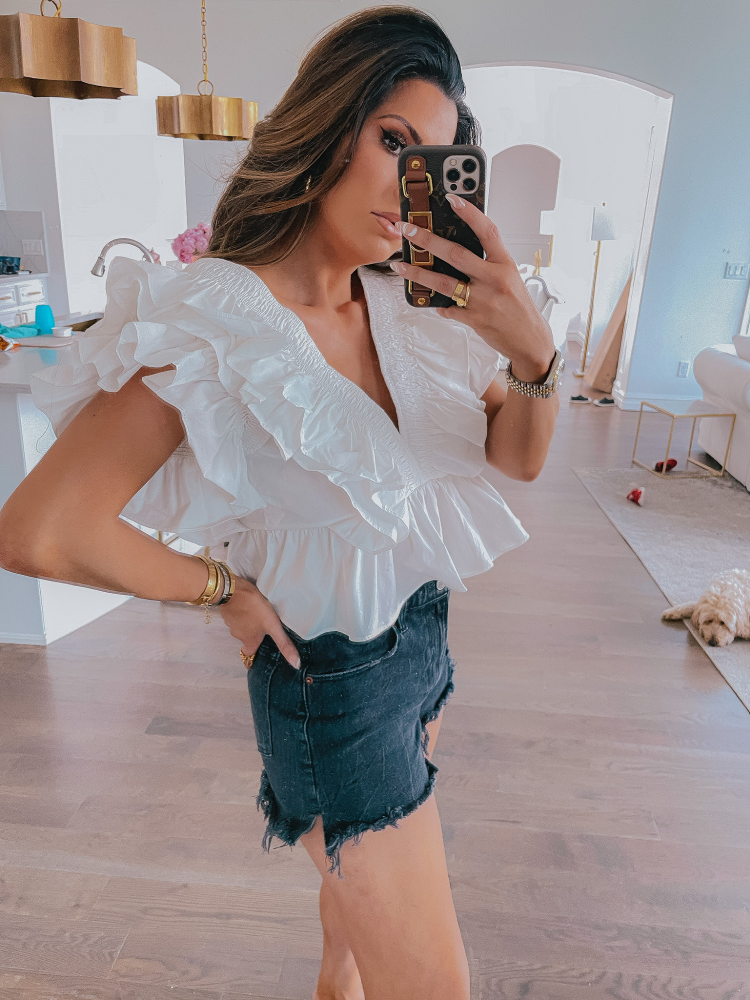 LTK Sales by popular US fashion blog, The Sweetest Thing: image of Emily Gemma wearing a white v-neck ruffle blouse with cutoff black denim shorts.