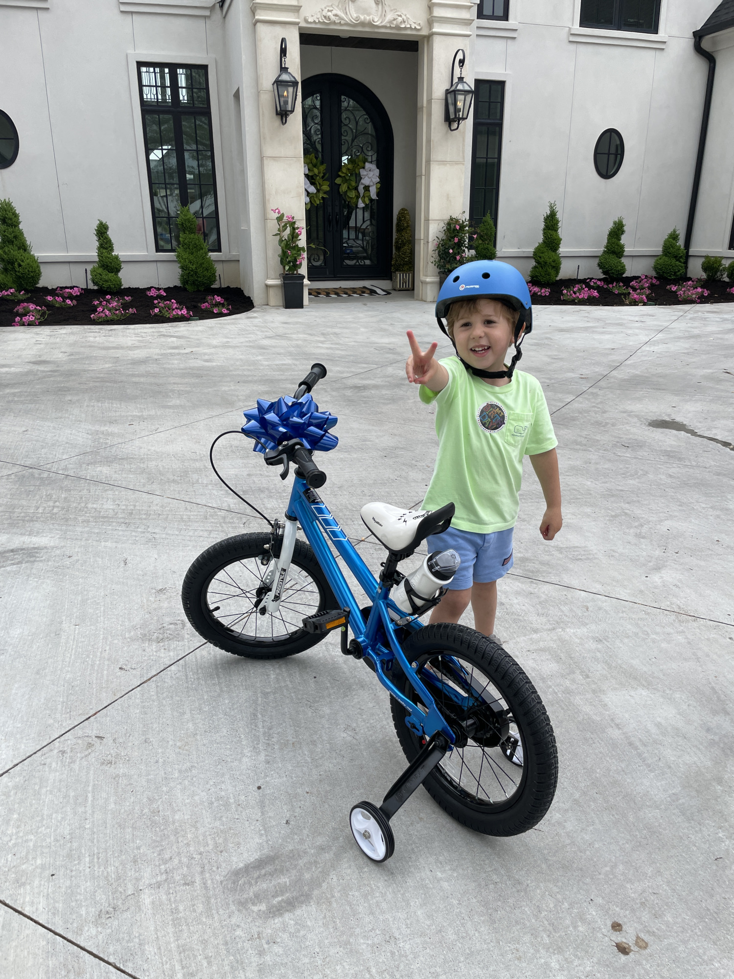 little boy gift ideas, bikes for little boys, bikes with training wheels, Luke gemma | Instagram Recap by popular US life and style blog, The Sweetest Thing: image of a little boy standing next to a blue bike with training wheels and holding up a the peace sign with his fingers and wearing a blue bike helmet, neon green shirt, and blue shorts.