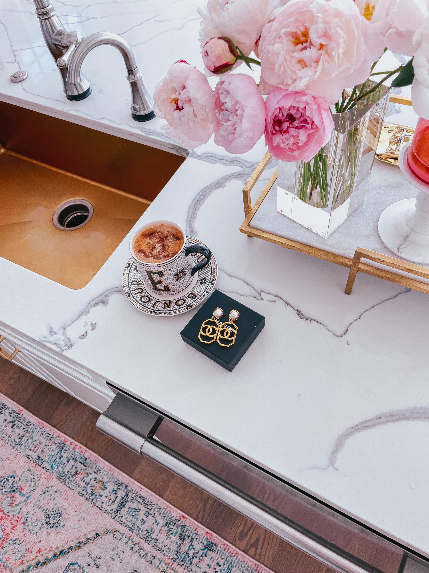 Emily-ann-gemma-kitchen-details-kitchen-decor-chanel-earrings-pretty-coffee-cup-peonies | Instagram Recap by popular US life and style blog, The Sweetest Thing: image of a black and white monogram Anthropologie mug and saucers next to a box of gold Chanel statement earrings a rose gold and white marble tray holding a clear glass vase filled with pink peonies.