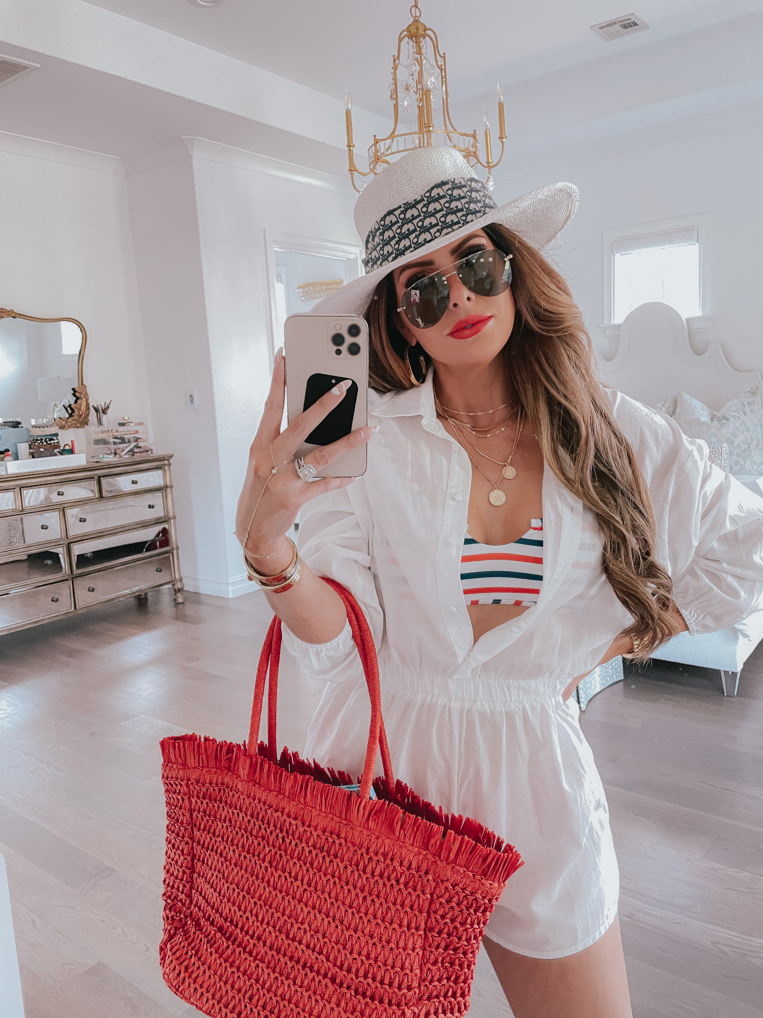 july 4 outfit inspiration 2021, pinterest july 4 outfit, dior scarf tied around hat, Emily gemma | June Instagram Recap by popular US fashion blog, The Sweetest Thing: image of Emily Gemma wearing a white straw hat, white romper, white, red and blue stripe swimsuit top and holding a red straw tote bag.
