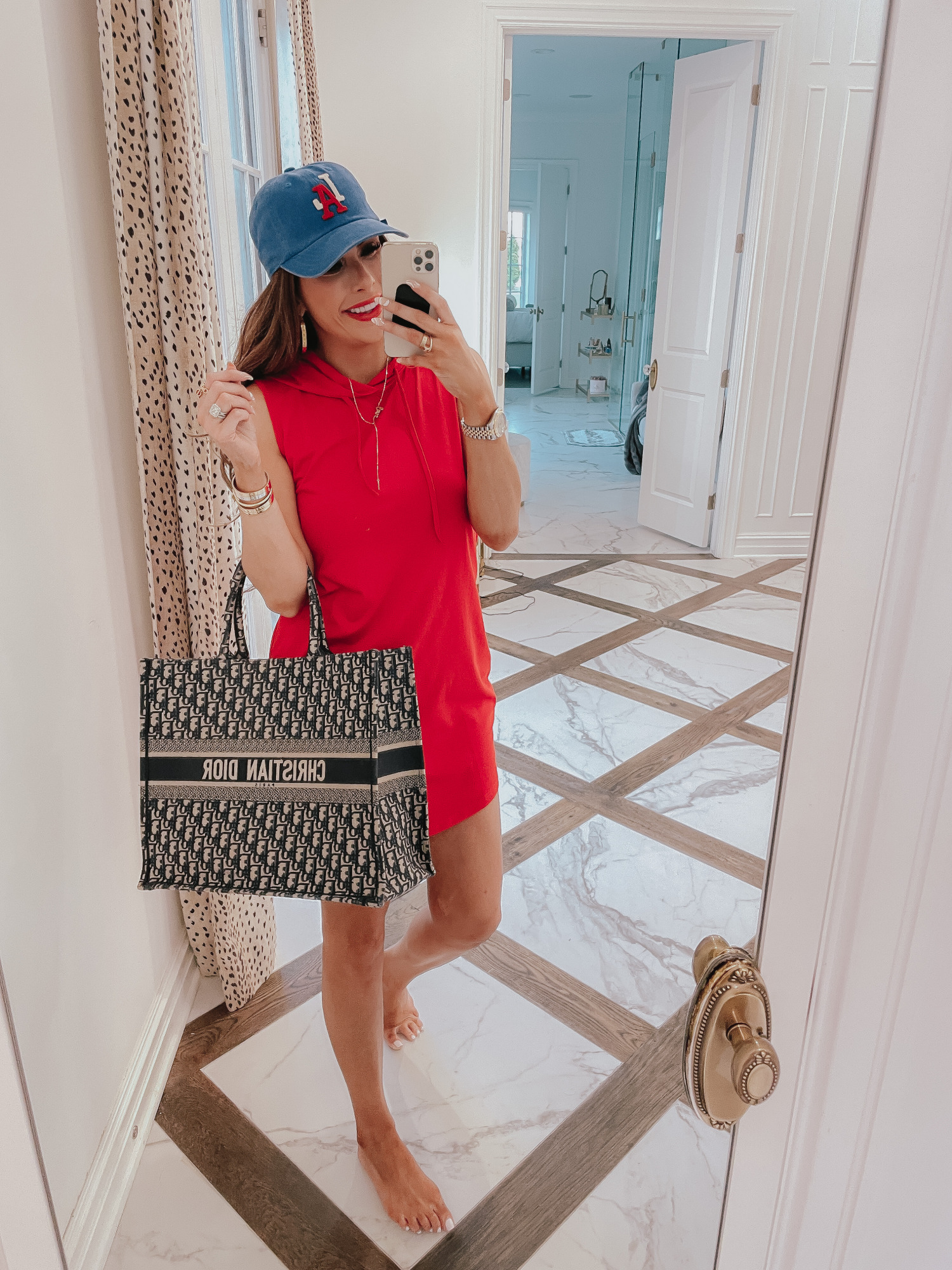 july 4 outfit inspiration 2021, pinterest july 4 outfit, gucci red lipstick, dior book tote navy, Emily gemma | June Instagram Recap by popular US fashion blog, The Sweetest Thing: image of Emily Gemma wearing a blue baseball cap, red sleeveless hoodie dress, and holding a Christian Dior tote bag.