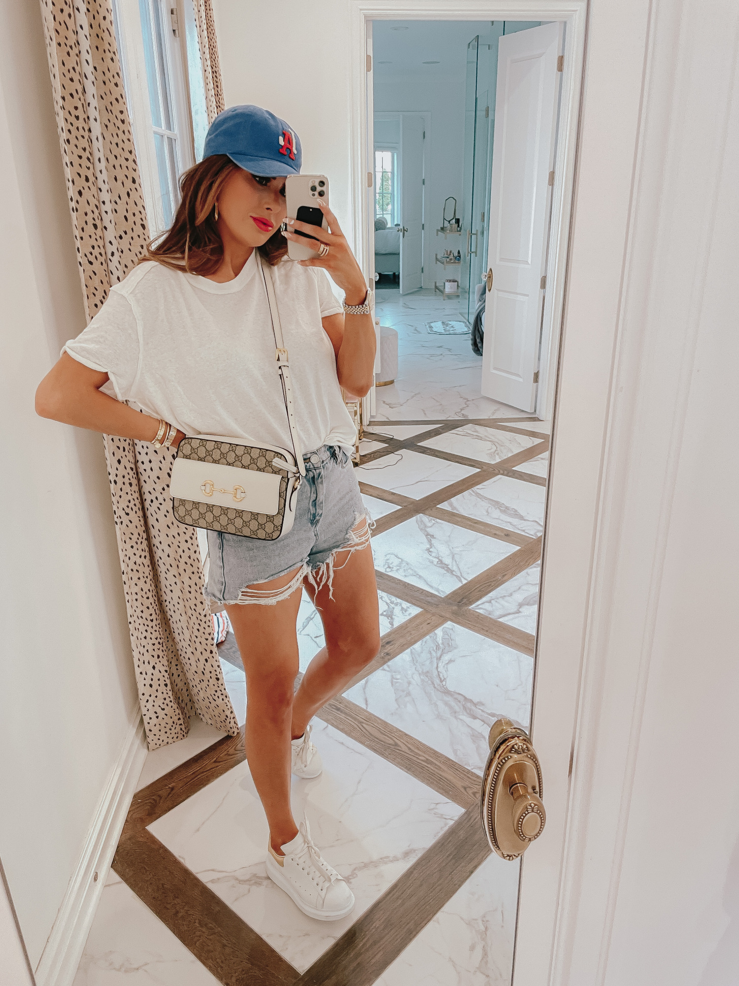 july 4 outfit inspiration 2021, pinterest july 4 outfit, gucci red lipstick, gucci 1955 horsebit crossbody, Emily gemma |  June Instagram Recap by popular US fashion blog, The Sweetest Thing: image of Emily Gemma wearing a blue baseball cap, white t-shirt, distressed shorts, and white sneakers.