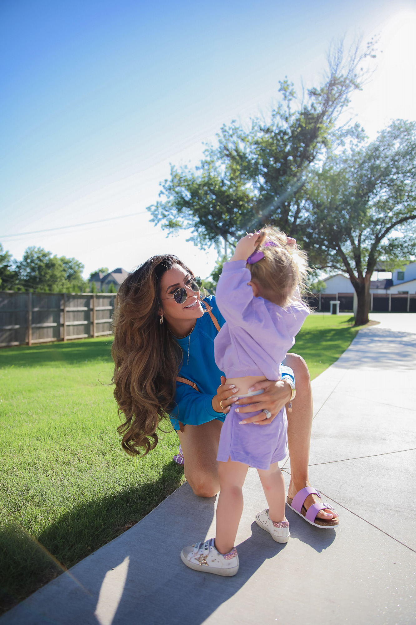walmart fashion blog, best walmart fashion outfits blog instagramer, emily gemma, scoop walmart womens fashion, birkinstock dupes-6 | June Instagram Recap by popular US fashion blog, The Sweetest Thing: image of Emily Gemma and her daughter Sophie standing together outside and wearing a blue sweatshirt, purple strap sandals, purple loungewear set, Golden Goose sneakers, and purple hair bows.