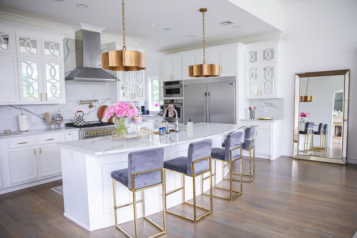 Spring Kitchen by popular US life and style blog: image of a kitchen with white cabinets, wood flooring, wooden light pendants, marble counter tops, gold and grey velvet bar stools, and light pink and blue runner rug.