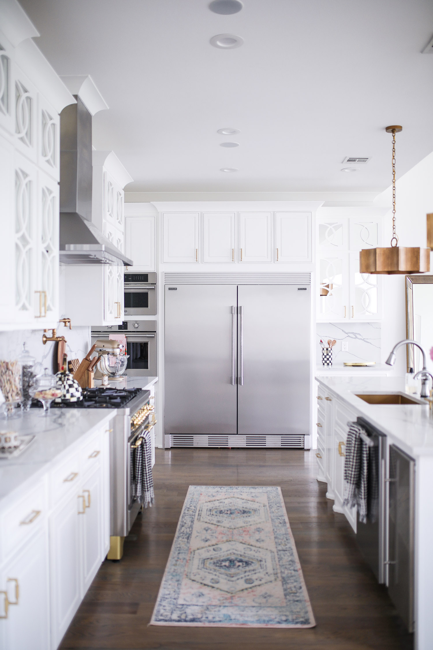 Spring Kitchen by popular US life and style blog: image of a kitchen with white cabinets, wood flooring, wooden light pendants, marble counter tops, and light pink and blue runner rug.