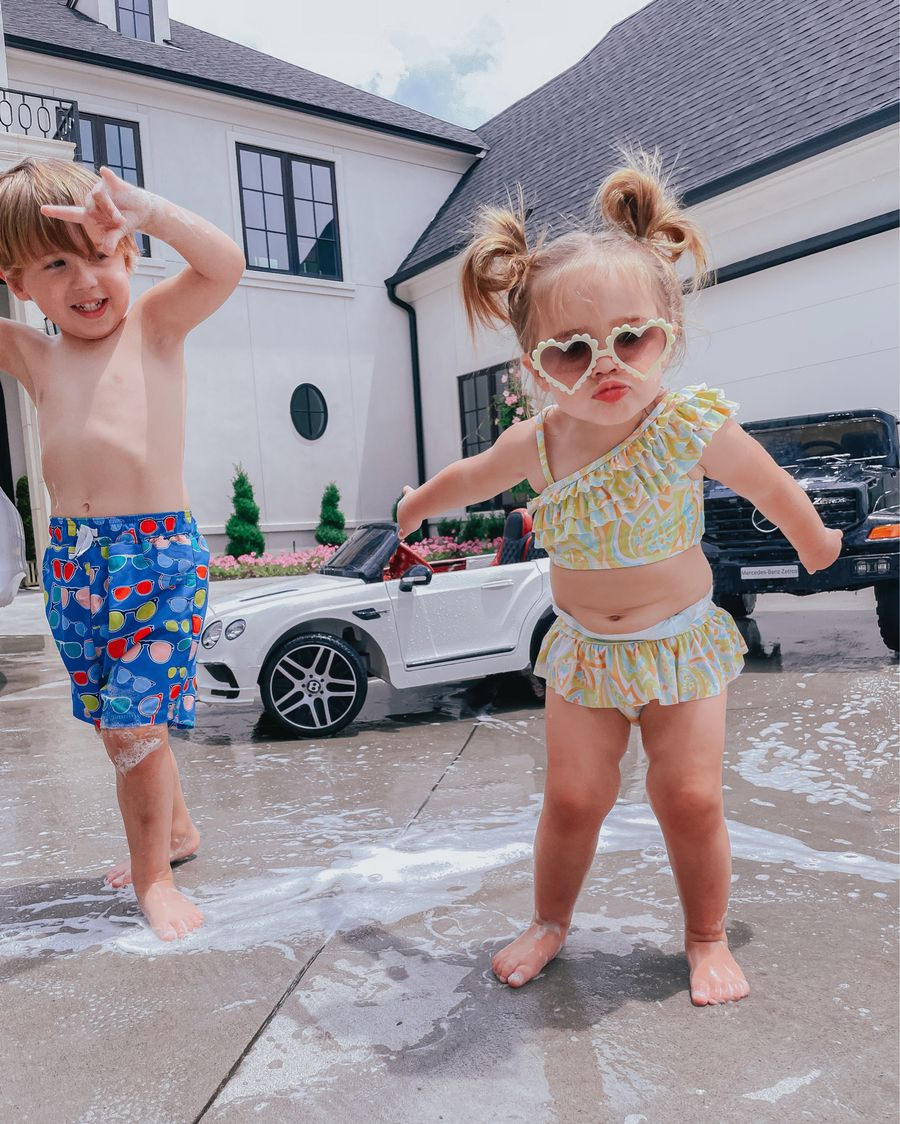 Luke and Sophia gemma, kids summer fun, little girl swimsuit, little girl sunglasses, little boy swimsuits, Emily ann gemma, Janie and jack | June Instagram Recap by popular US fashion blog, The Sweetest Thing: image of a young boy and girl wearing their swimsuits standing next to their mini cars.