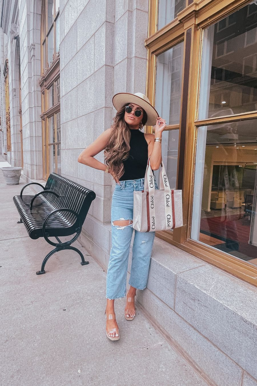 Summer Outfit by popular US fashion blog, The Sweetest Thing: image of Emily Gemma standing outside in front of a building with gold framed windows and wearing a cream fedora hat, BP mock neck tank, Agolde jeans, Steve Madden clear strap espadrilles, and holding a Chloe tote bag.