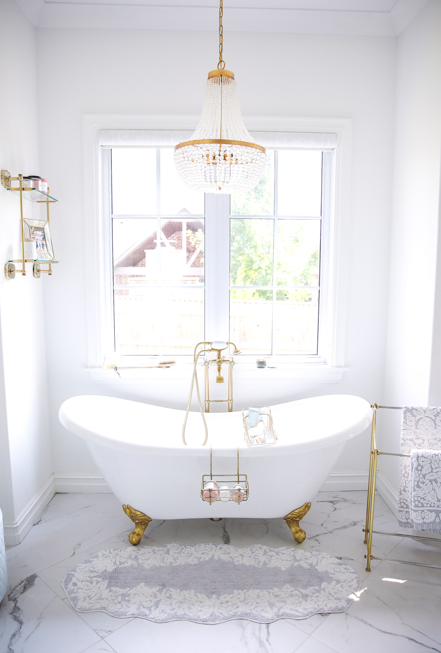 Emily gemma master bathroom, Nordstrom anniversary sale 2021 beauty must haves, anthropologie bathrom decor 2021, pinterest bathroom all white gold   Instagram Recap by popular US life and style blog, The Sweetest Thing: image of a white and gold clawfoot tub with a gold and crystal chandelier and gold towel rack.
