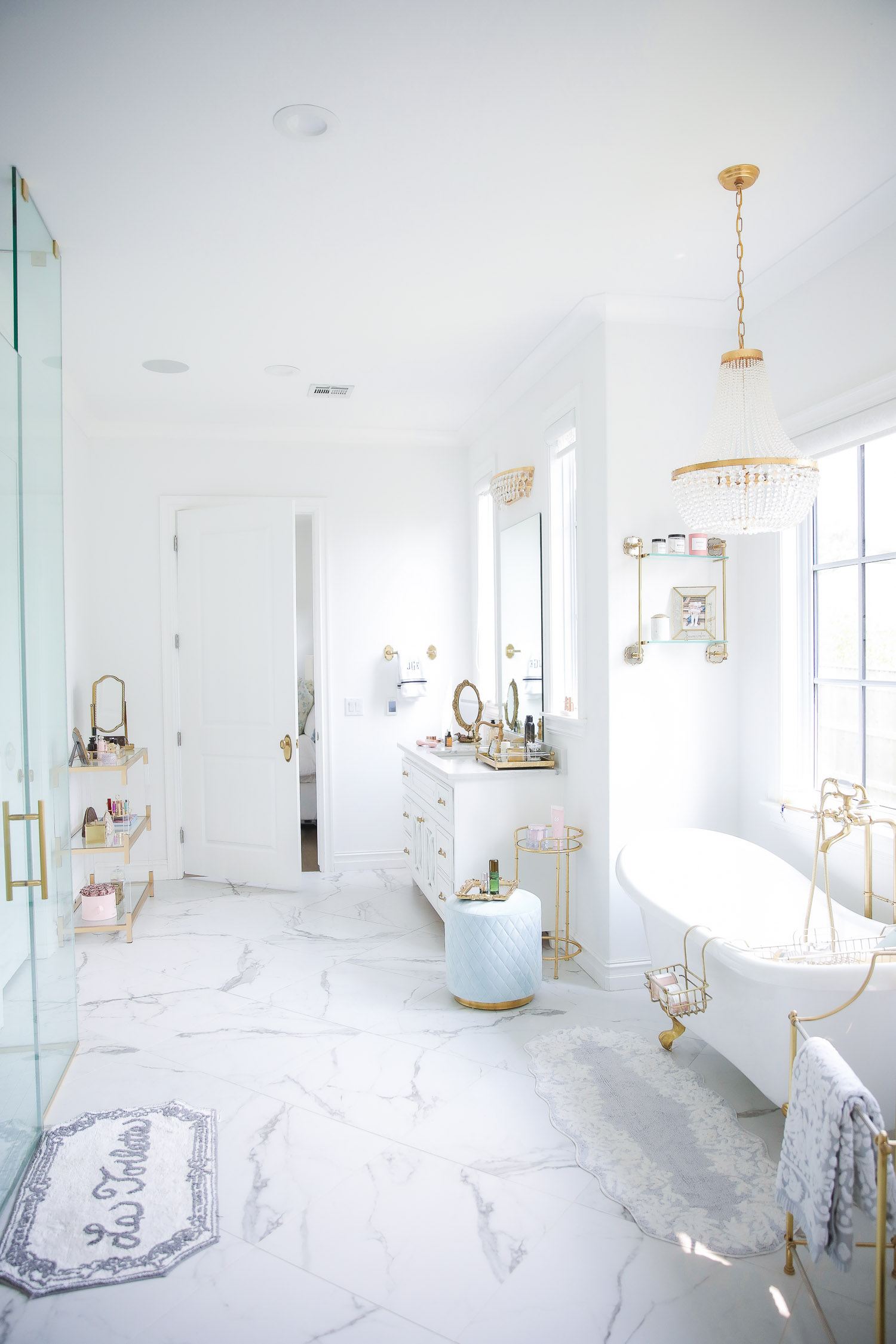 Emily gemma master bathroom, Nordstrom anniversary sale 2021 beauty must haves, anthropologie bathrom decor 2021, pinterest bathroom all white gold | Nordstrom Anniversary Sale 2021 by popular US life and style blog, The Sweetest Thing: image of a master bedroom with marble flooring, white and gold clawfoot tub, gold and crystal chandelier, gold metal towel stand and walk in shower.