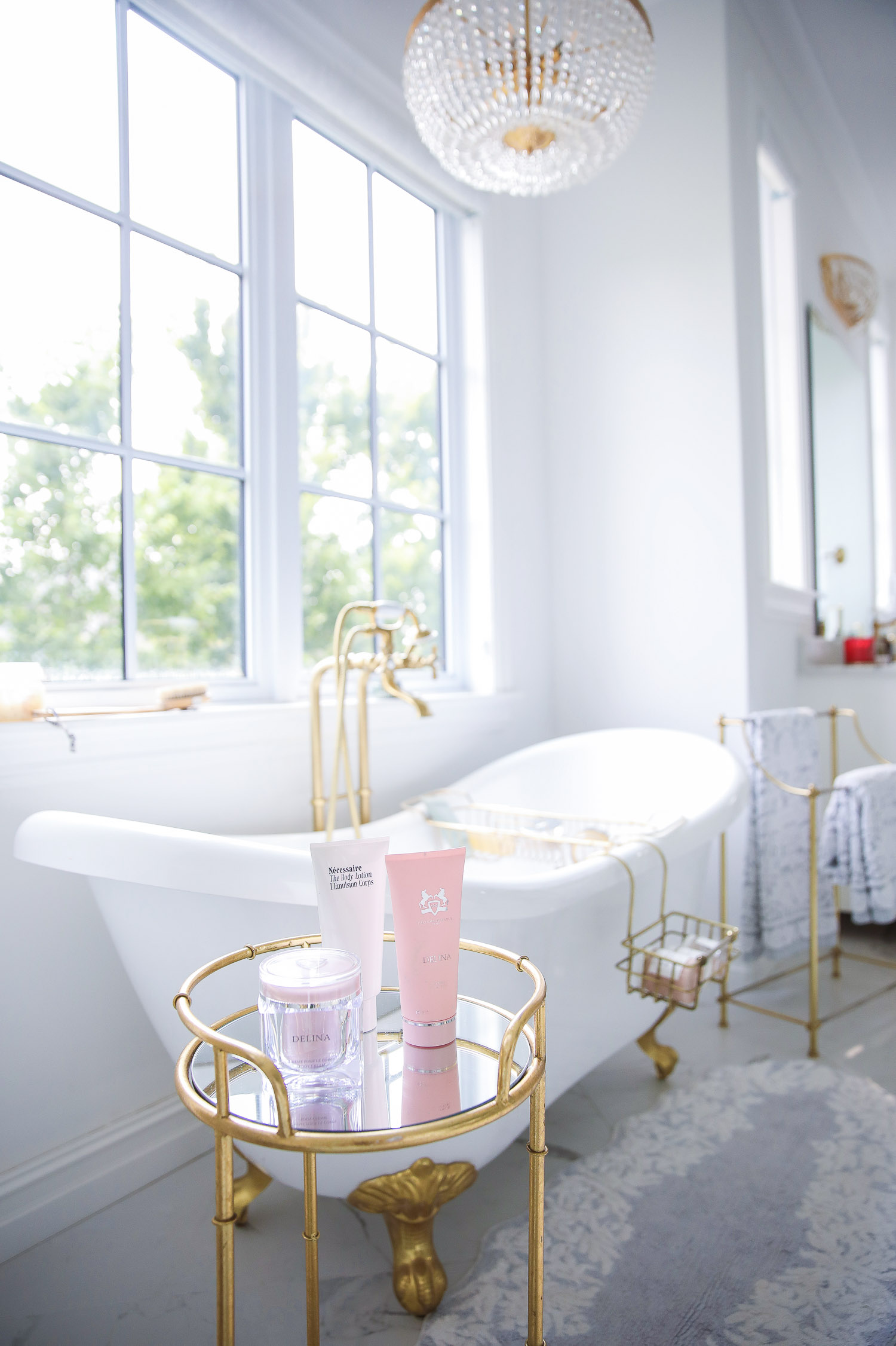 Delina Parfum de Marly set NSALE 2021, Emily gemma master bathroom, Nordstrom anniversary sale 2021 beauty must haves, anthropologie bathrom decor 2021, pinterest bathroom all white gold | Nordstrom Anniversary Sale 2021 by popular US life and style blog, The Sweetest Thing: image of a white and gold clawfoot tub next to a gold and glass table filled with skincare products.