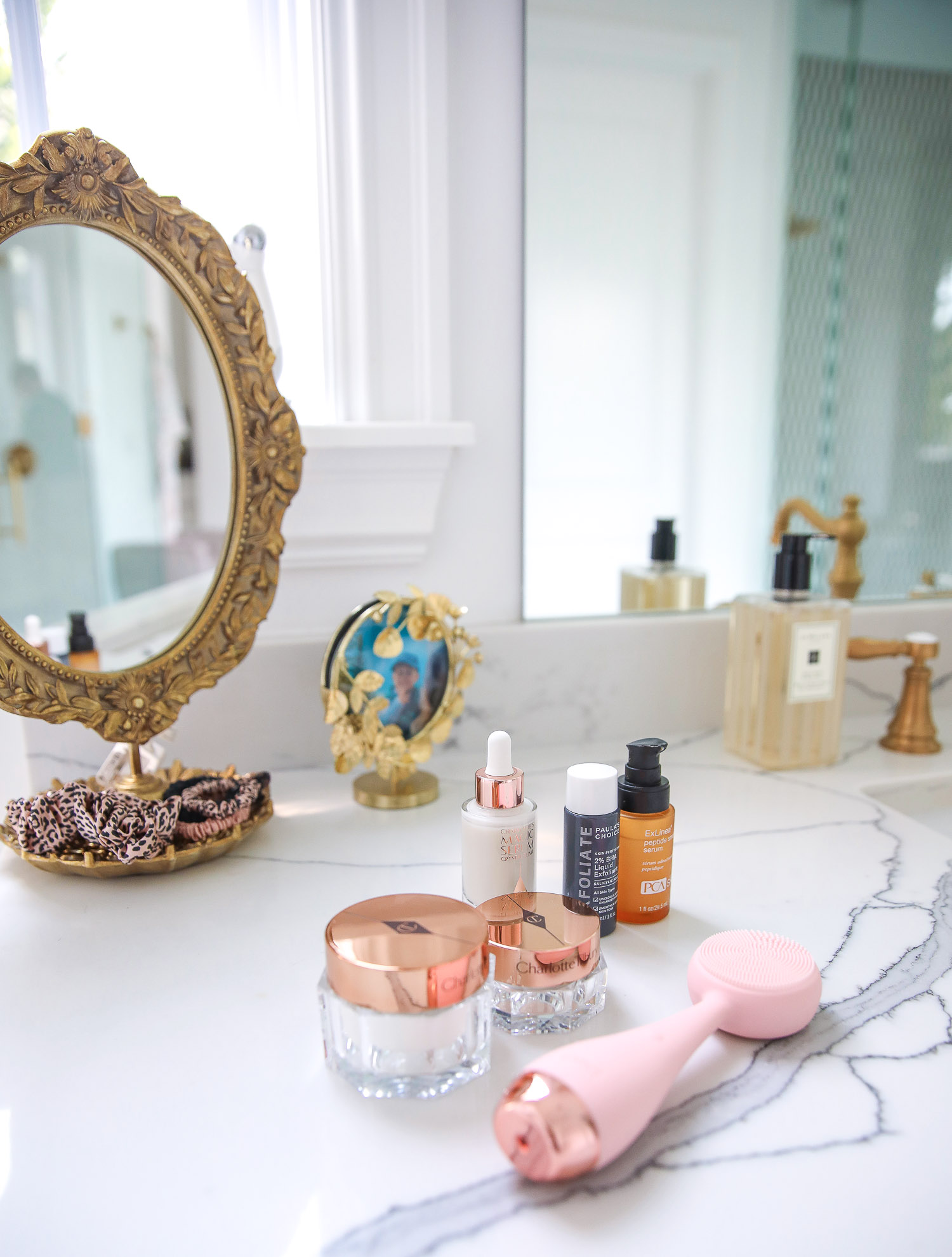 Emily gemma master bathroom, Nordstrom anniversary sale 2021 beauty must haves, anthropologie bathrom decor 2021, pinterest bathroom all white gold | Nordstrom Anniversary Sale 2021 by popular US life and style blog, The Sweetest Thing: image of a silicone face scrubber, gold filigree hand mirror, and skincare products on a white marble counter.