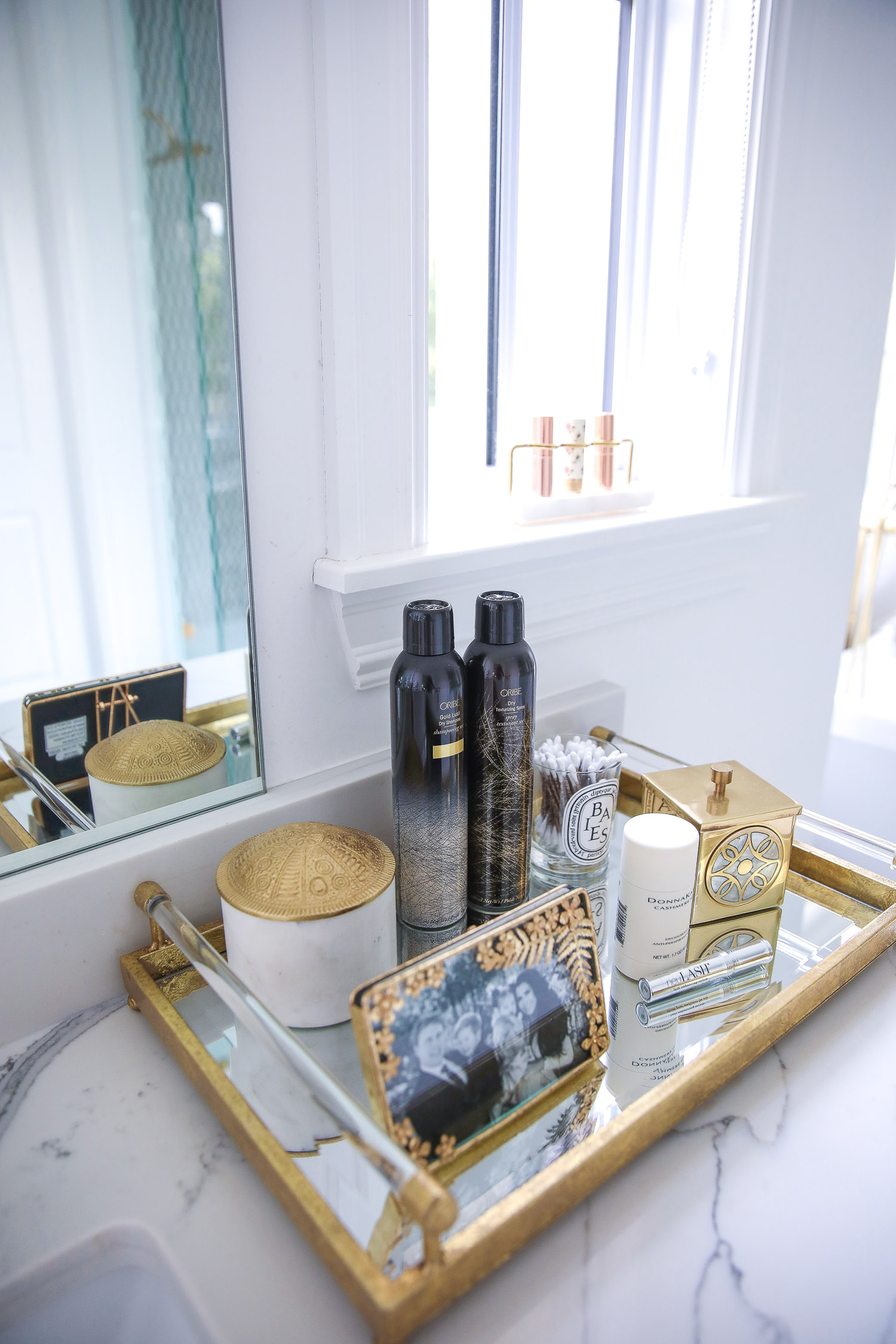 Anthropologie home decor summer 2021, oribe dry texture spray NSALE 2021 | Nordstrom Anniversary Sale 2021 by popular US life and style blog, The Sweetest Thing: image of a gold metal and mirrored tray filled with a white candle, Oribe dry texture spray bottles and gold picture Fram with a black and white family photograph.