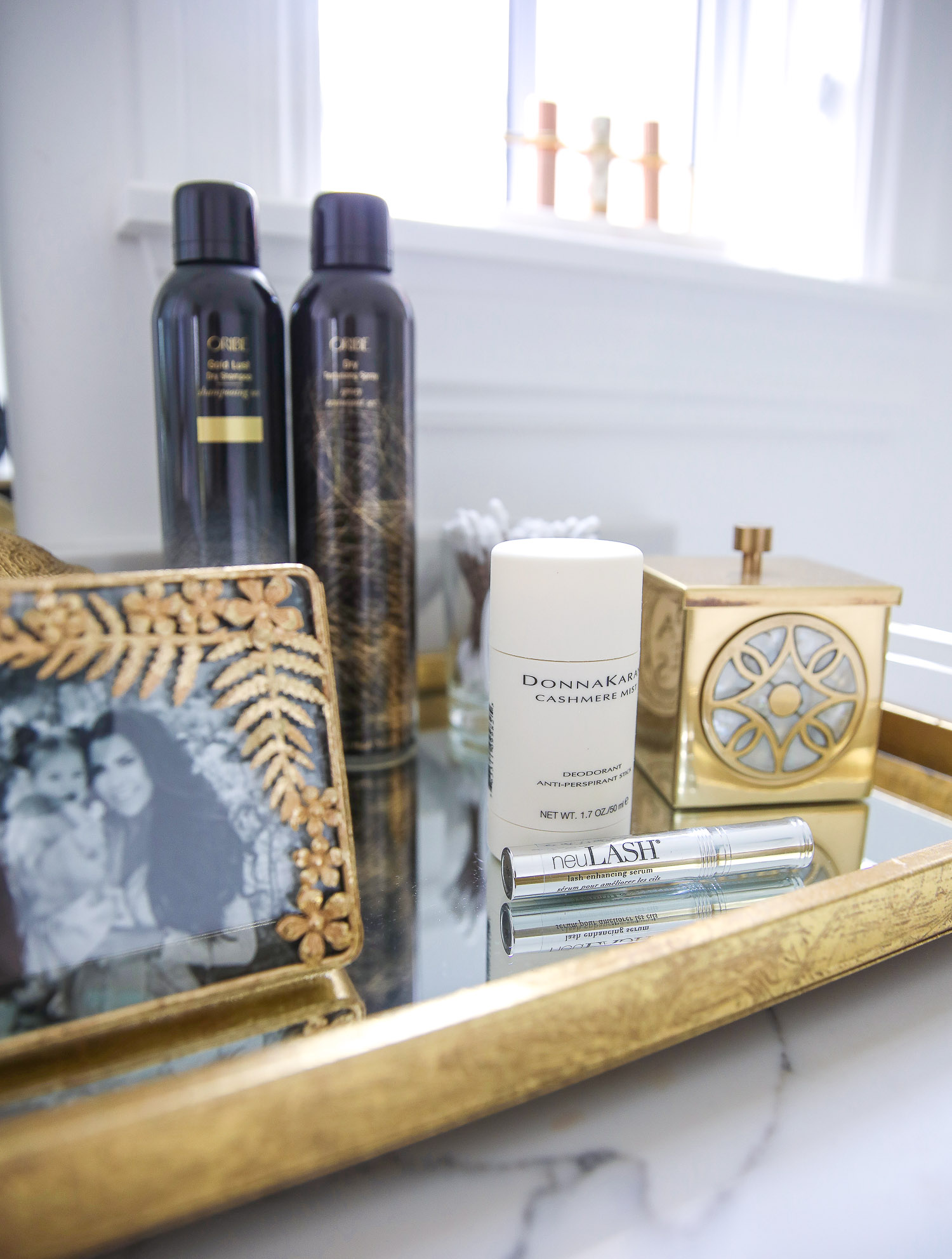 Emily gemma master bathroom, Nordstrom anniversary sale 2021 beauty must haves, anthropologie bathrom decor 2021, pinterest bathroom all white gold | Nordstrom Anniversary Sale 2021 by popular US life and style blog, The Sweetest Thing: image of a gold metal and mirrored tray with Oribe dry texture spray bottles, Donna Karan Cashmere beauty product, neu lash mascara, and gold picture frame with a black and white family photo.