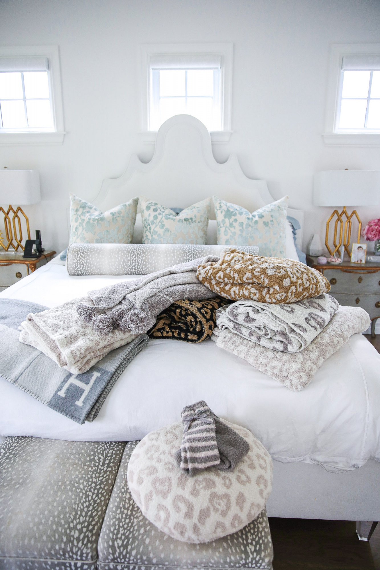Emily gemma master bedroom, little design co pillows bolster, Nordstrom anniversary sale home must haves 2021, nsale barefoot dreams blanket pillows review, parfum de marly set | Nordstrom Anniversary Sale 2021 by popular US life and style blog, The Sweetest Thing: image of a master bedroom with Barefoot Dreams blankets and Barefoot Dreams socks on a bed with a white fabric headboard and white bedding next to  mirrored night stands with gold lamps.