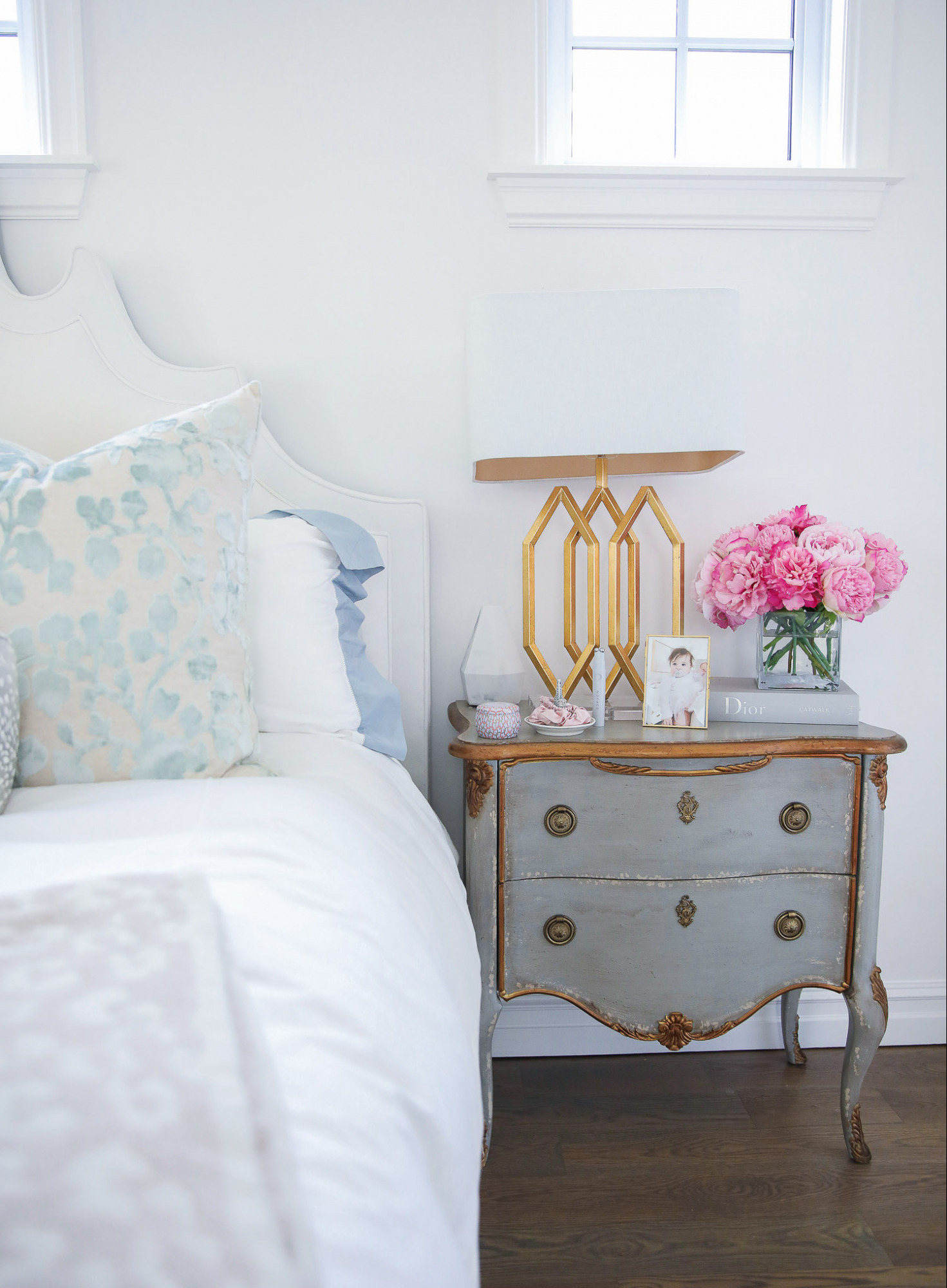 hooker furniture master bedroom, master bedroom Inspo interest, Emily Gemma master bedroom, Anthropologie mirrors, perfume trays, Pinterest home Inspo 2021 |  Nordstrom Anniversary Sale 2021 by popular US life and style blog, The Sweetest Thing: image of a master bedroom with a mirrored night stand containing a gold base lamp, glass vase filled with pink peonies, Voulspa candle, and pink silk scrunchies on a white ceramic ring holder.