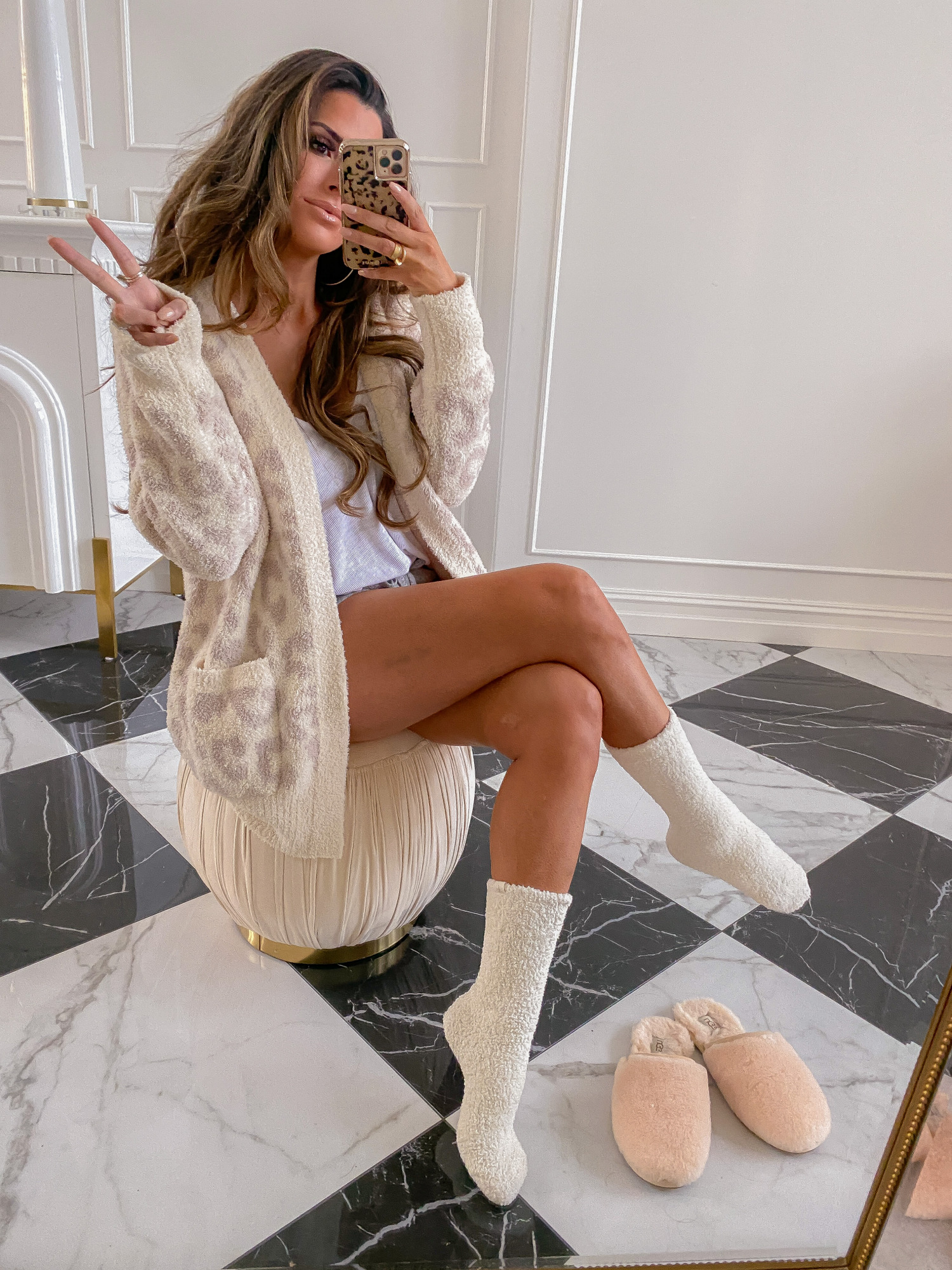 https://www.thesweetestthingblog.com/app/uploads/2021/07/Nsale-2021-must-haves-Nordstrom-Anniversary-Sale-2021-picks-emily-gemma-Nordstrom-sale-Barefoot-dreams-cardigan-socks-What-to-buy-NSALE-2021 |  Nordstrom Anniversary Sale by popular US fashion blog, The Sweetest Thing: image of Emily Gemma wearing a pair of Barefoot Dreams socks and a Barefoot Dreams sweater while sitting on a tan tuft ottoman.