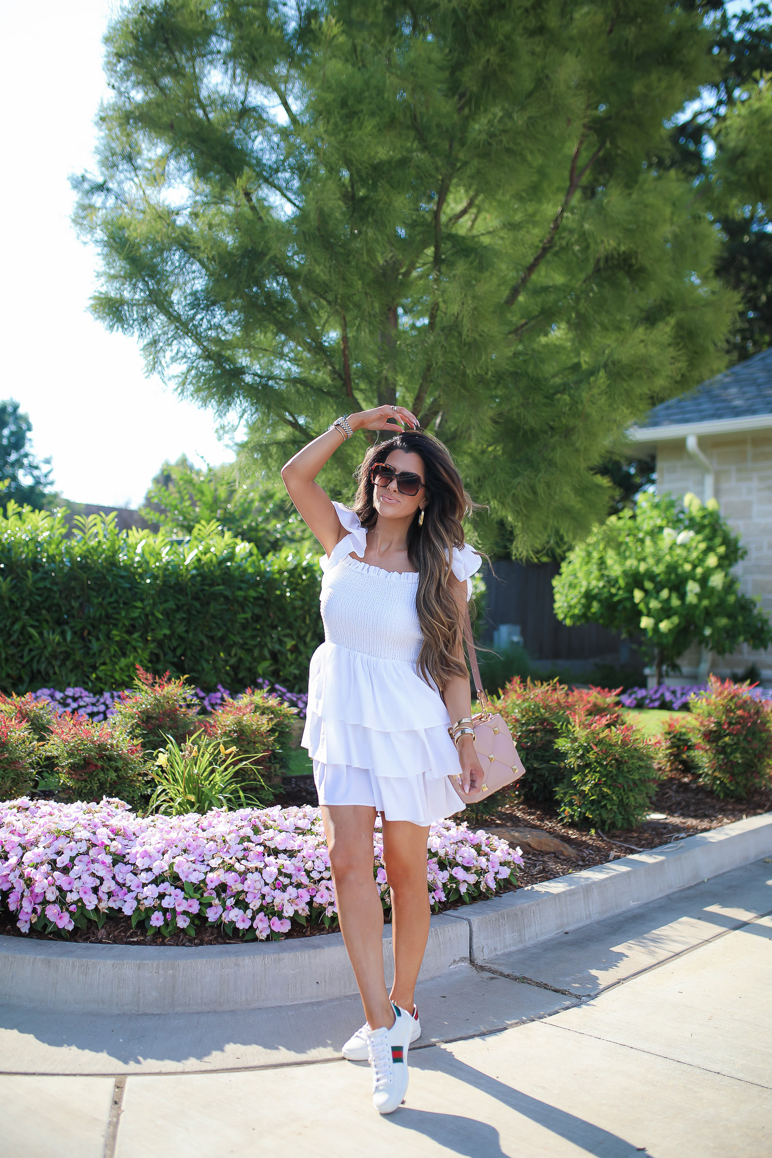 Love Shack Fancy by popular US fashion blog, The Sweetest Thing: image of Emily Gemma wearing a white Express dress, Express sunglasses, Rolex watch, gold bracelets, gold hoop earrings, Gucci sneakers, and holding a Valentino bag.
