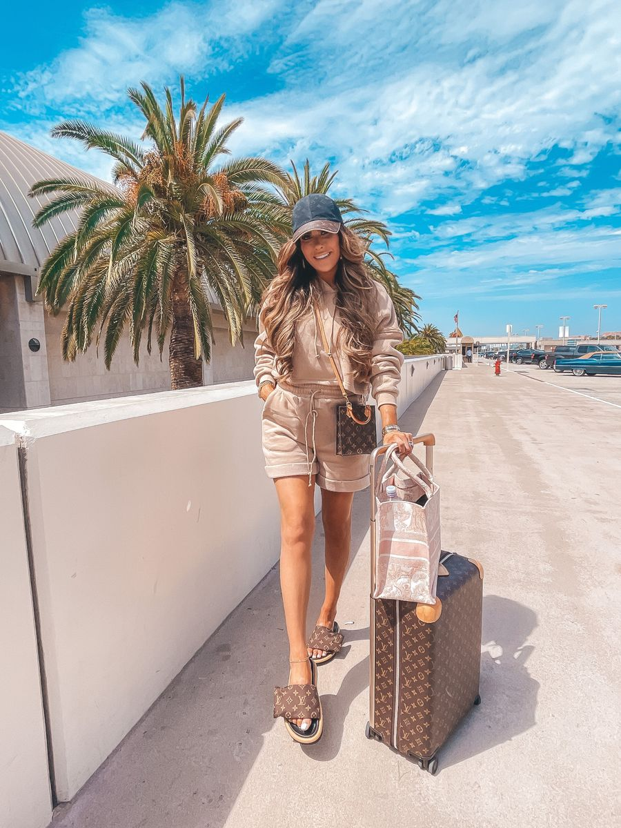 Emily ann gemma, travel outfit ideas, airport outfit ideas, Louis Vuitton luggage, Christian Dior Book Tote, Louis Vuitton Pillow Slides, Louis Vuitton Ballcap, Sweatshirt and Shorts outfit, matching loungewear set   Instagram Recap by popular US life and style blog, The Sweetest Thing: image of Emily Gemma wearing a matching tan loungewear set, black and brown Louis Vuitton ball cap, Lousi Vuitton crossbody bag, and Louis Vitton slide sandals.