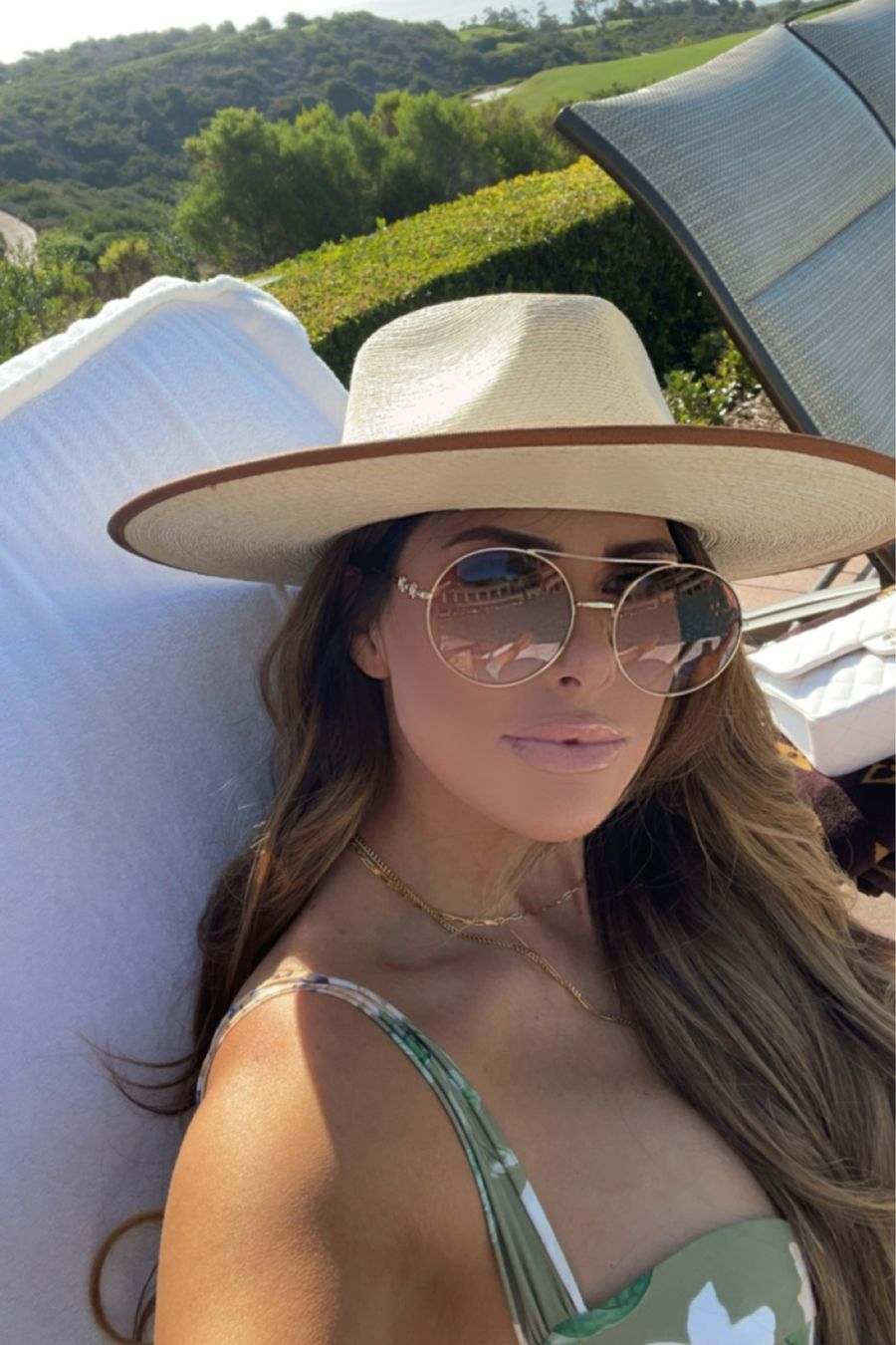 Emily ann gemma, summer style, floral bikini, gucci sunglasses, poolside styles, gucci handbag   Instagram Recap by popular US life and style blog, The Sweetest Thing: image of Emily Gemma sitting on a poolside lounge chair and wearing a straw fedora hat, round frame sunglasses, and green and white floral print swimsuit.