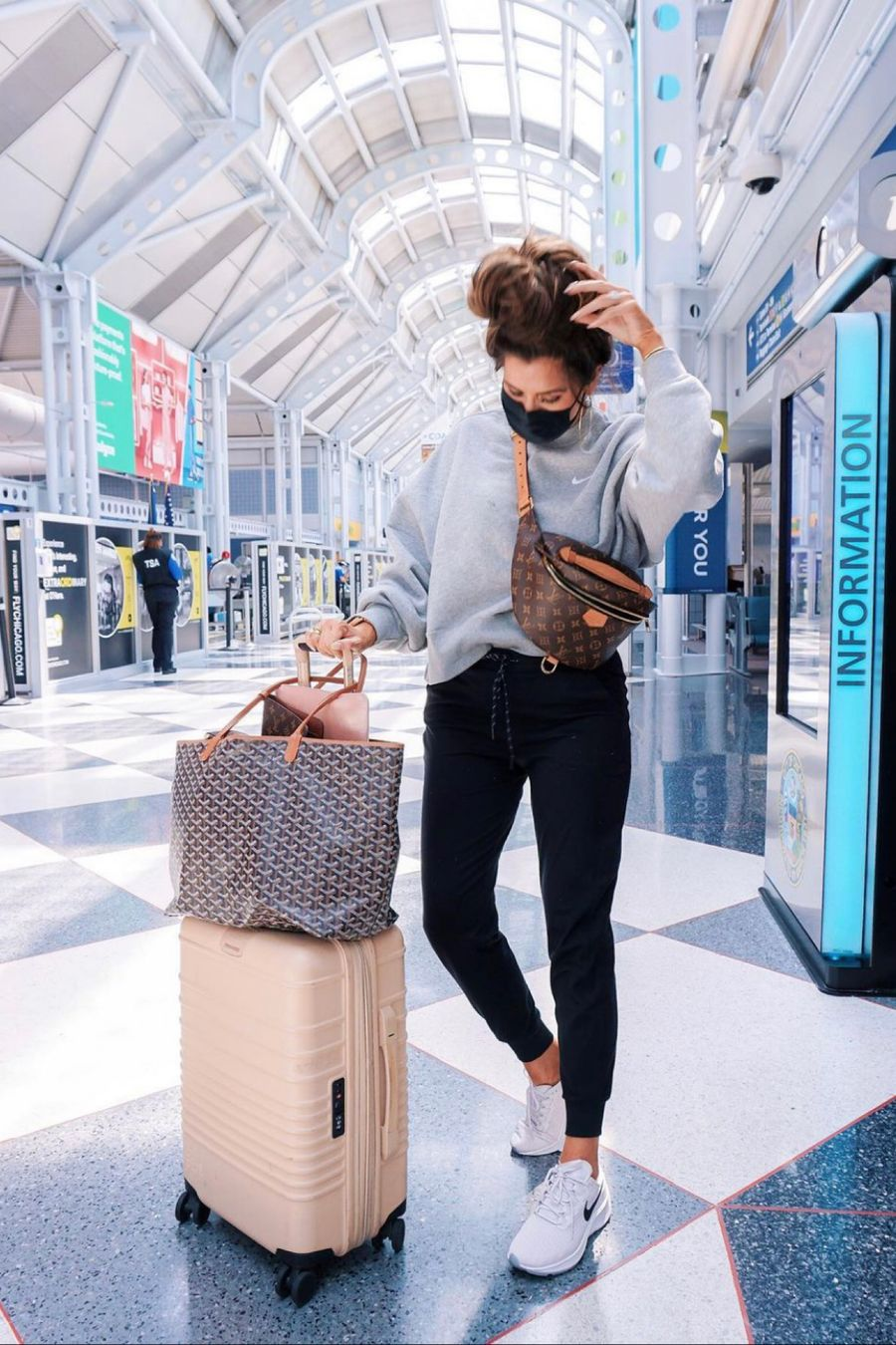 Emily ann gemma travel outfit ideas, airport outfits, airport travel style, Emily gemma, best loungewear, Louis Vuitton bum bum bag, nike sneakers, nordstrom sale, carry-on suitcase, goyard bag   Instagram Recap by popular US life and style blog, The Sweetest Thing: image of Emily Gemma wearing a grrey sweatshirt, black jogger pants, white Nike sneakers and standing next to her luggage.