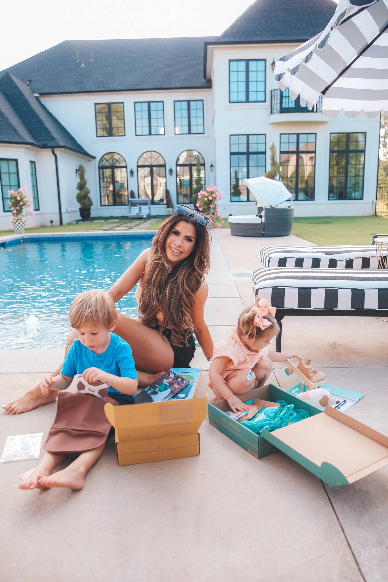 Emily Ann Gemma Family, Luke Gemma, Sophia Gemma, Kids Toys, Kids Educational Toys, KiwiCo. , Best toys and activities for kids, summer activities for kids   Instagram Recap by popular US life and style blog, The Sweetest Thing: image of Emily Gemma and her two kids sitting by their pool and opening some KiwiCo boxes.