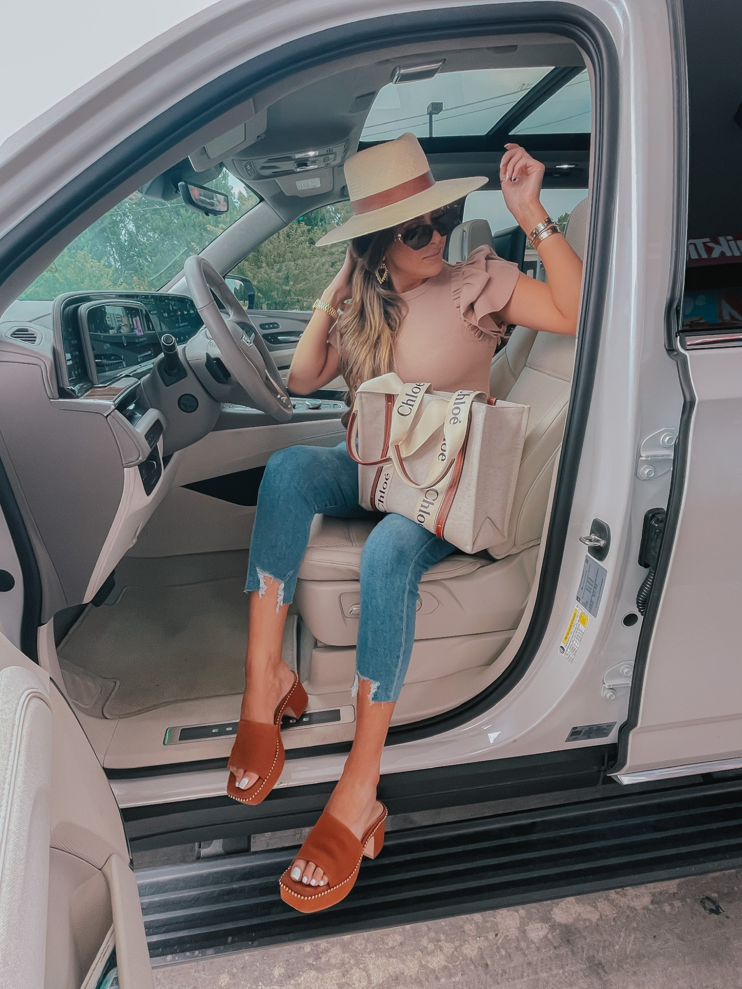 Emily Ann Gemma, Emily Gemma Outfit Ideas, Chloe Tote Bag, Express Jeans, Express Top, Ruffle Sleeve Tank Top, Antonio Melanie Slides, Fall Shoes   Instagram Recap by popular US life and style blog, The Sweetest Thing: image of Emily Gemma sitting her SUV and wearing a Express tan ruffle sleeve top, Express distressed jeans, Gianni Bini mule sandals, felt fedora hat and Chloe bag.