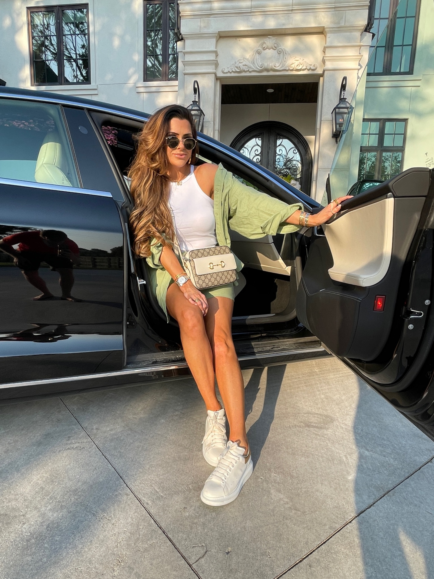 Emily Ann Gemma, Summer Outfit Ideas, Matching Shorts Outfit, White Tank Top, Alexander McQueen Sneakers, Gucci Handbag, Missguided, Affordable Outfit Ideas   Instagram Recap by popular US life and style blog, The Sweetest Thing: image of Emily Gemma sitting in a black Sudan and wearing a white tank, oversize green shirts, and white sneakers.