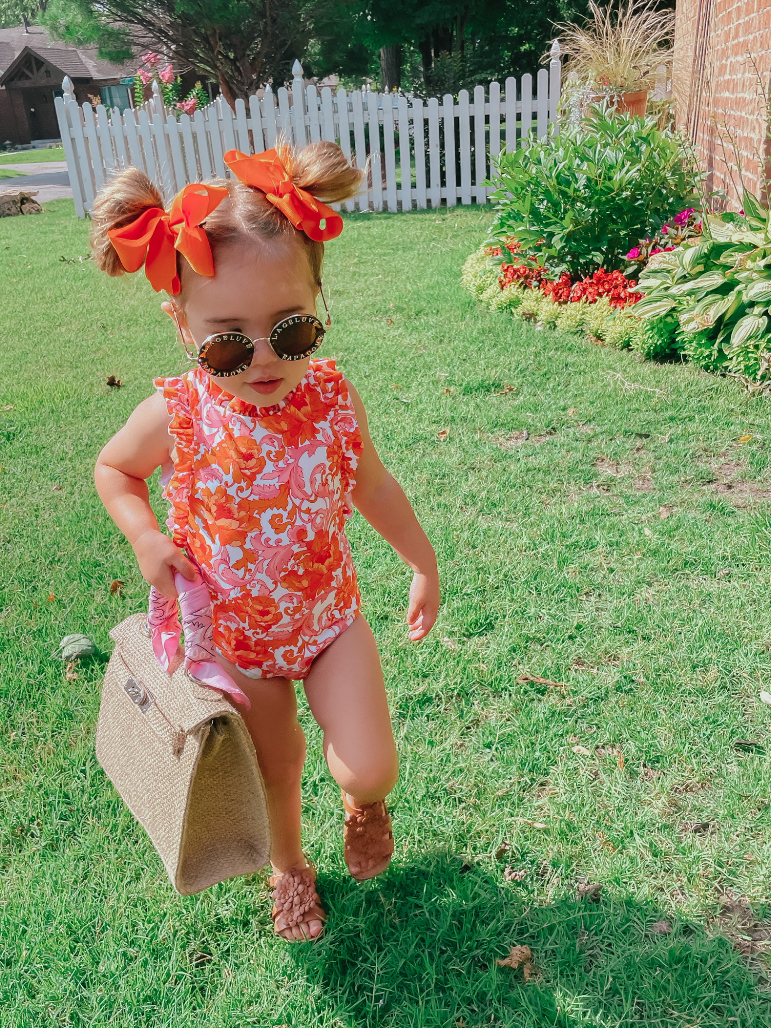 Sophia Gemma, Toddler Swimsuit, Toddler Bows, Swimwear for little girls, Kids Sunglasses, Baby Girl Summer Outfit Ideas   Instagram Recap by popular US life and style blog, The Sweetest Thing: image of a little girl wearing an orange and pink floral print Janie and Jack swimsuit, Zara sandals, orange hair bows, and holding a woven handbag.