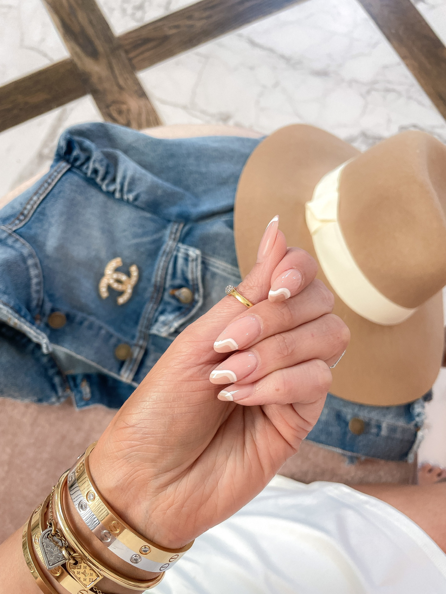 Emily ann gemma, emily gemma nail inspiration, nude nails, nude nail designs, fall nail designs 2021, cartier bracelet stack, denim jacket, chanel brooch, wool hat   Instagram Recap by popular US life and style blog, The Sweetest Thing: image of Emily Gemma with a nude abstract design manicure.