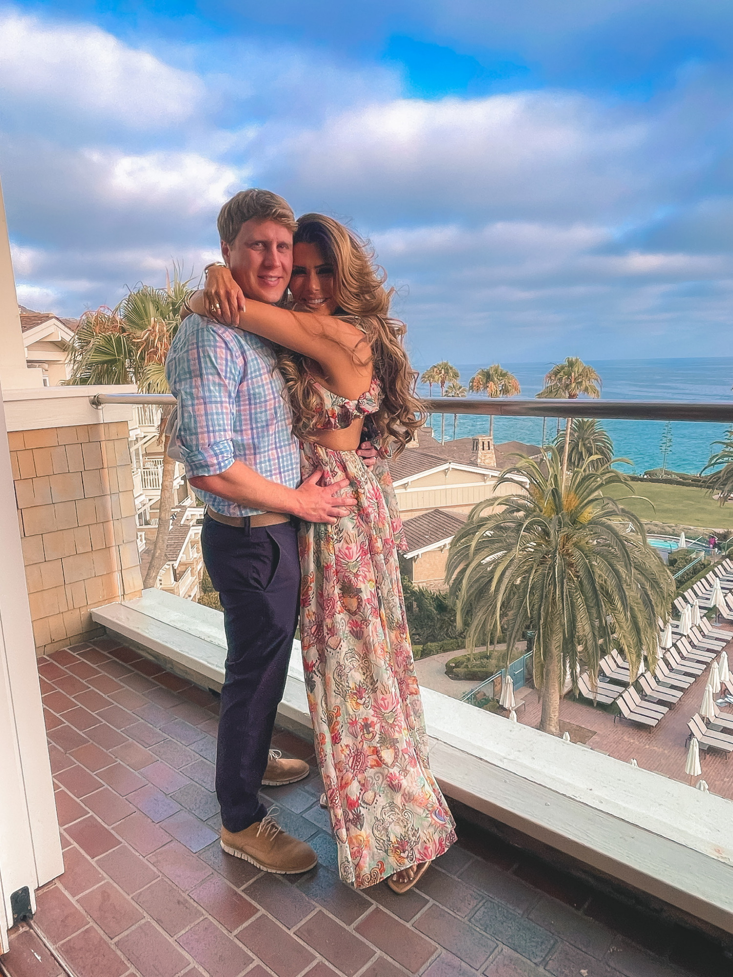 Emily and John gemma, Zimmermann dress, vacation outfit ideas   Instagram Recap by popular US life and style blog, The Sweetest Thing: image of Emily Gemma wearing a tropical print Zimmerman dress and standing with her arms wrapped around her husband while standing on a deck with an ocean view.