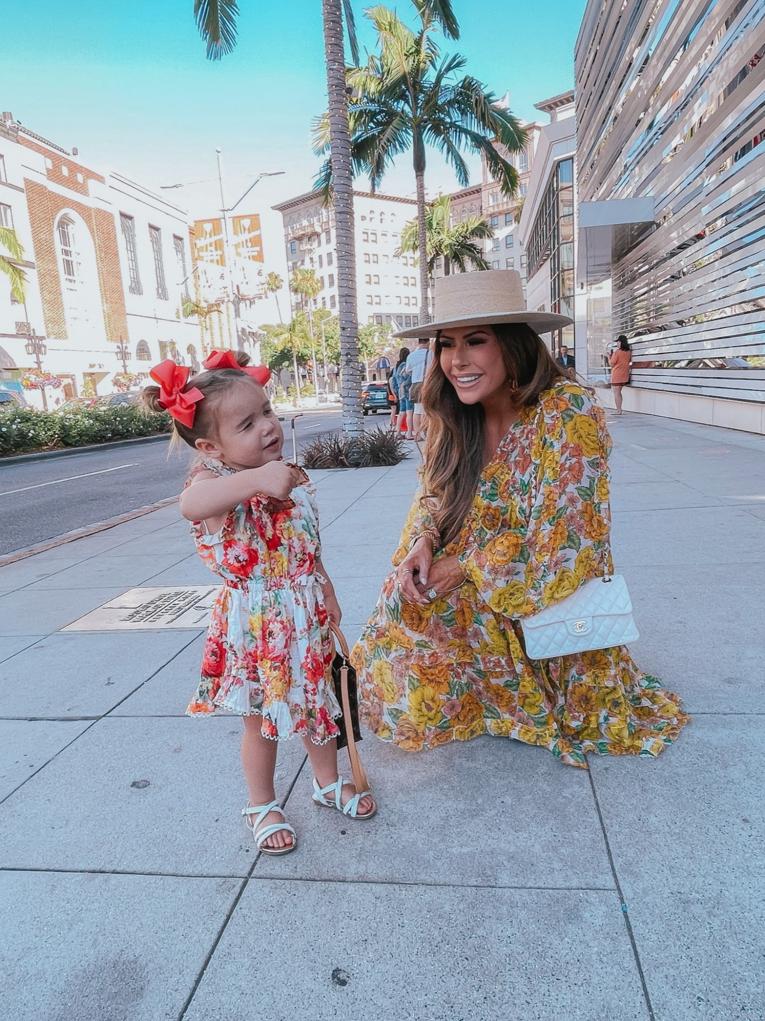 rodeo drive, mommy daughter shopping trip, Beverly Hills, Zimmermann dress, Zimmermann kids, Zimmermann mommy and daughter matching outfits, Chanel handbag, comfortable wedge sandals   Instagram Recap by popular US life and style blog, The Sweetest Thing: image of Emily Gemma wearing a floral print mini dress, Lack of Color boater hat, and white quilted Chanel purse and standing outside with her daughter Sophie wearing a floral print dress, white strap sandals, and red hair bows.