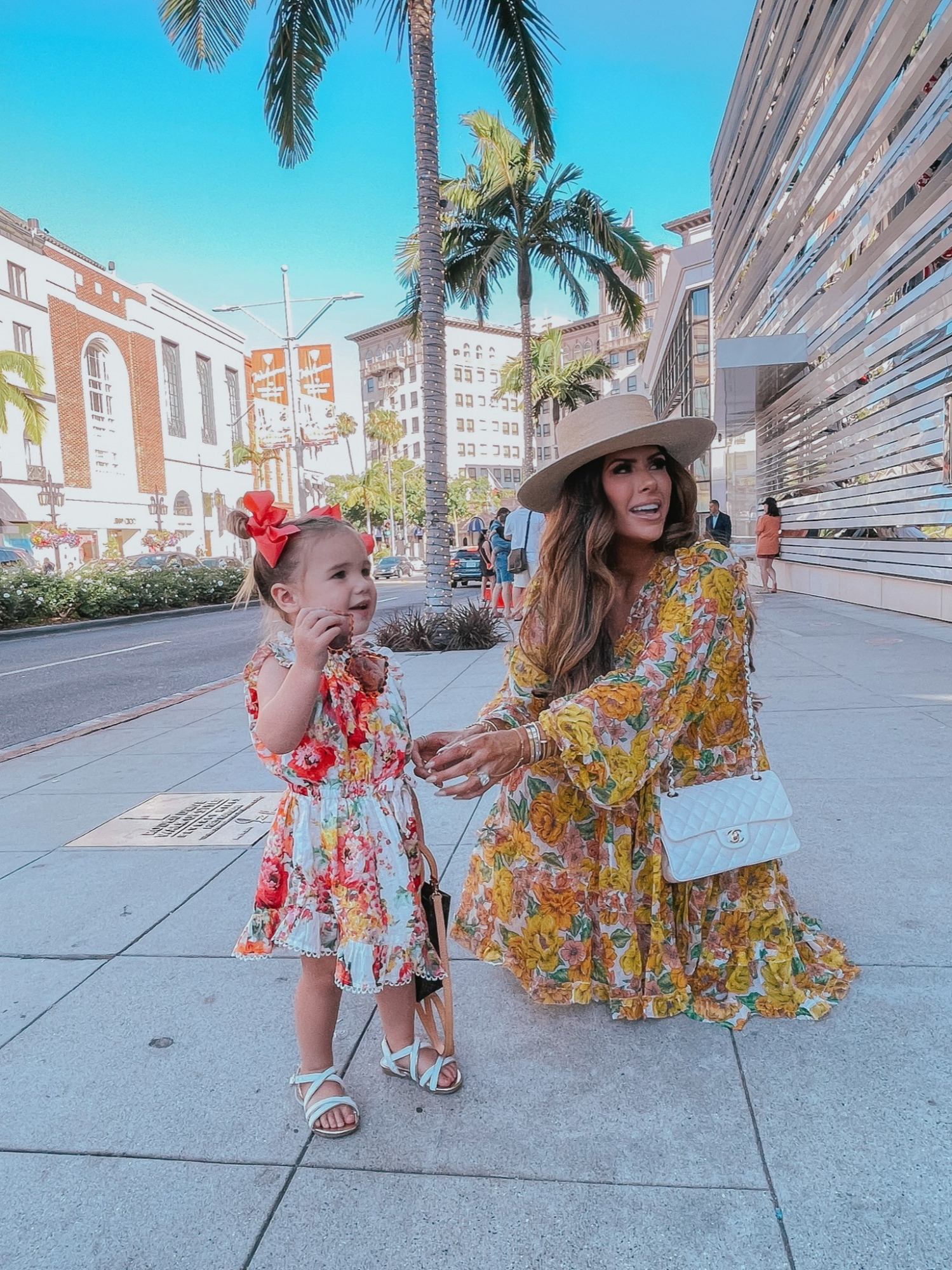 Instagram Recap by popular US life and style blog, The Sweetest Thing: image of Emily Gemma wearing a floral print mini dress, Lack of Color boater hat, and white quilted Chanel purse and standing outside with her daughter Sophie wearing a floral print dress, white strap sandals, and red hair bows.