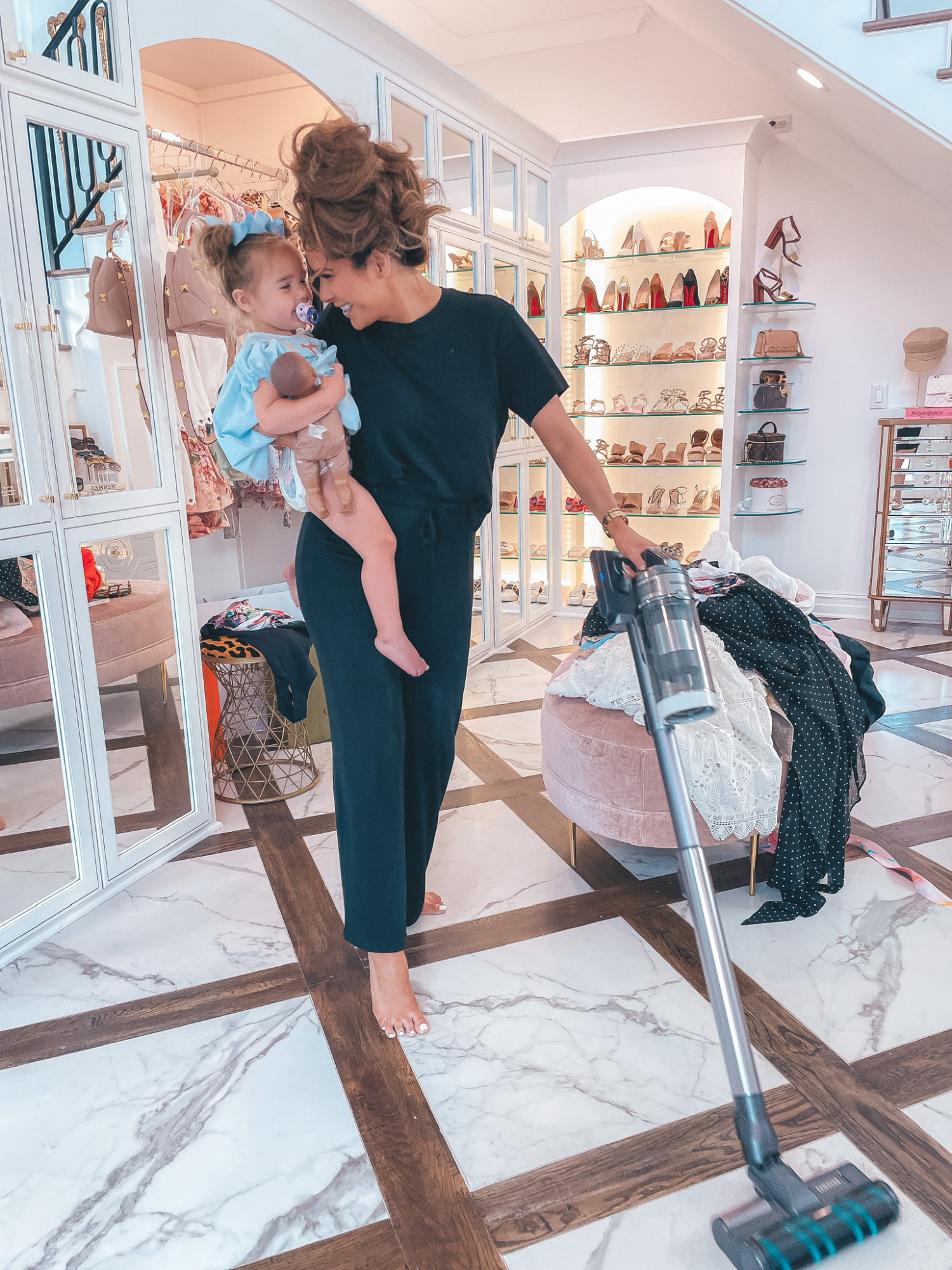 Emily ann gemma, work from home outfit, best loungewear, Nordstrom loungewear, soft pajamas, best cordless vacuum, Emily ann gemma | June Instagram Recap by popular US fashion blog, The Sweetest Thing:holding her young daughter while wearing a black t-shirt and black jogger pants and vacuuming her floor.