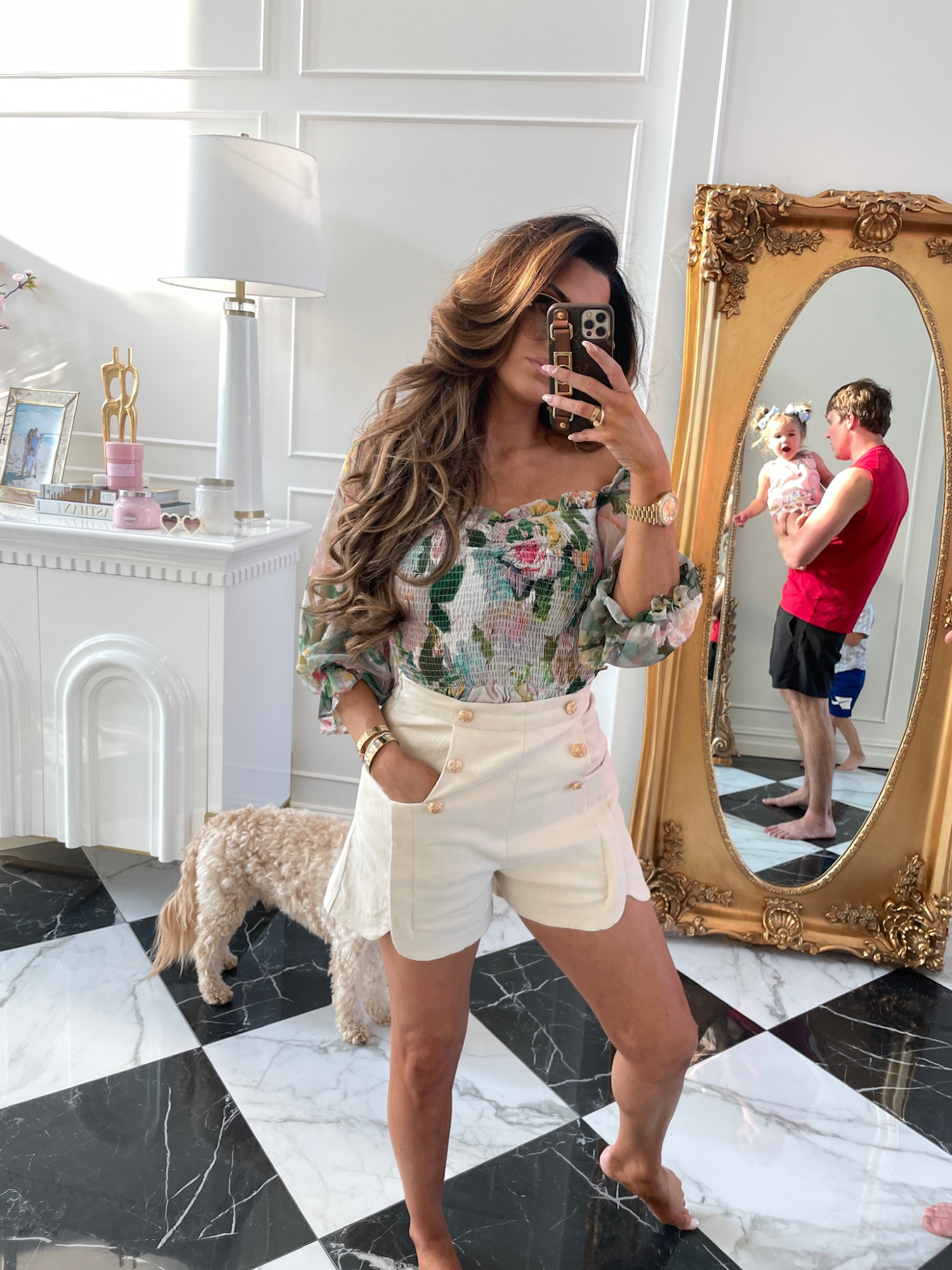 Emily ann gemma, floral blouse, cream shorts with gold buttons, white shorts, summer outfit ideas, Zimmerman dupe top | June Instagram Recap by popular US fashion blog, The Sweetest Thing: image of Emily Gemma wearing a floral print off the should top and high waisted scallop shorts.