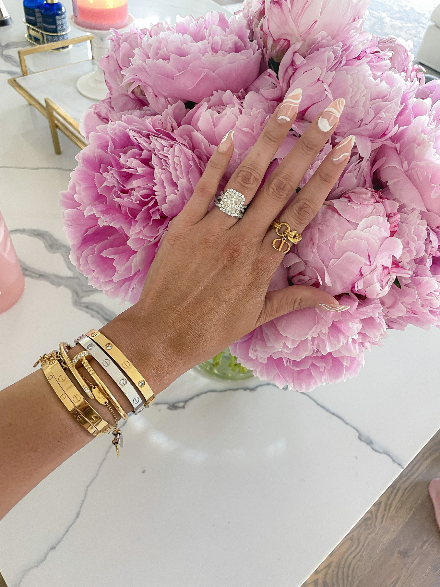 Emily ann gemma engagement ring, radiant cut engagement ring, Cartier bracelet, wrist bracelet stack, dior ring, pink peonies, Emily ann gemma | June Instagram Recap by popular US fashion blog, The Sweetest Thing: image of Emily Gemma wearing a radiant cut engagement ring, gold bracelets, and gold ring.