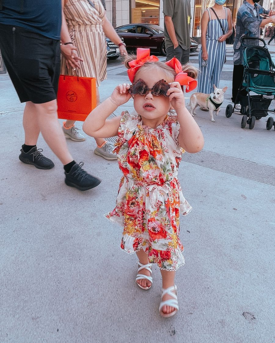 Sophia Gemma, Zimmermann Kids, Floral Dress for Little Girls, Bows for Little Girls, Kids Sunglasses   Instagram Recap by popular US life and style blog, The Sweetest Thing: image of a young girl wearing red hair bows, a floral print dress, heart frame sunglasses, and white strap sandals.