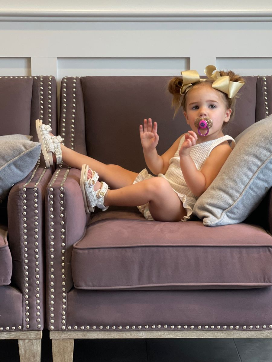 Little girls fashion, Sophia gemma, toddler style, toddler fashion, toddler girl fashion    Instagram Recap by popular US life and style blog, The Sweetest Thing: image of a little girl sitting in a armchair and wearing gold bows, cream color sleeveless romper, and silver sandals.