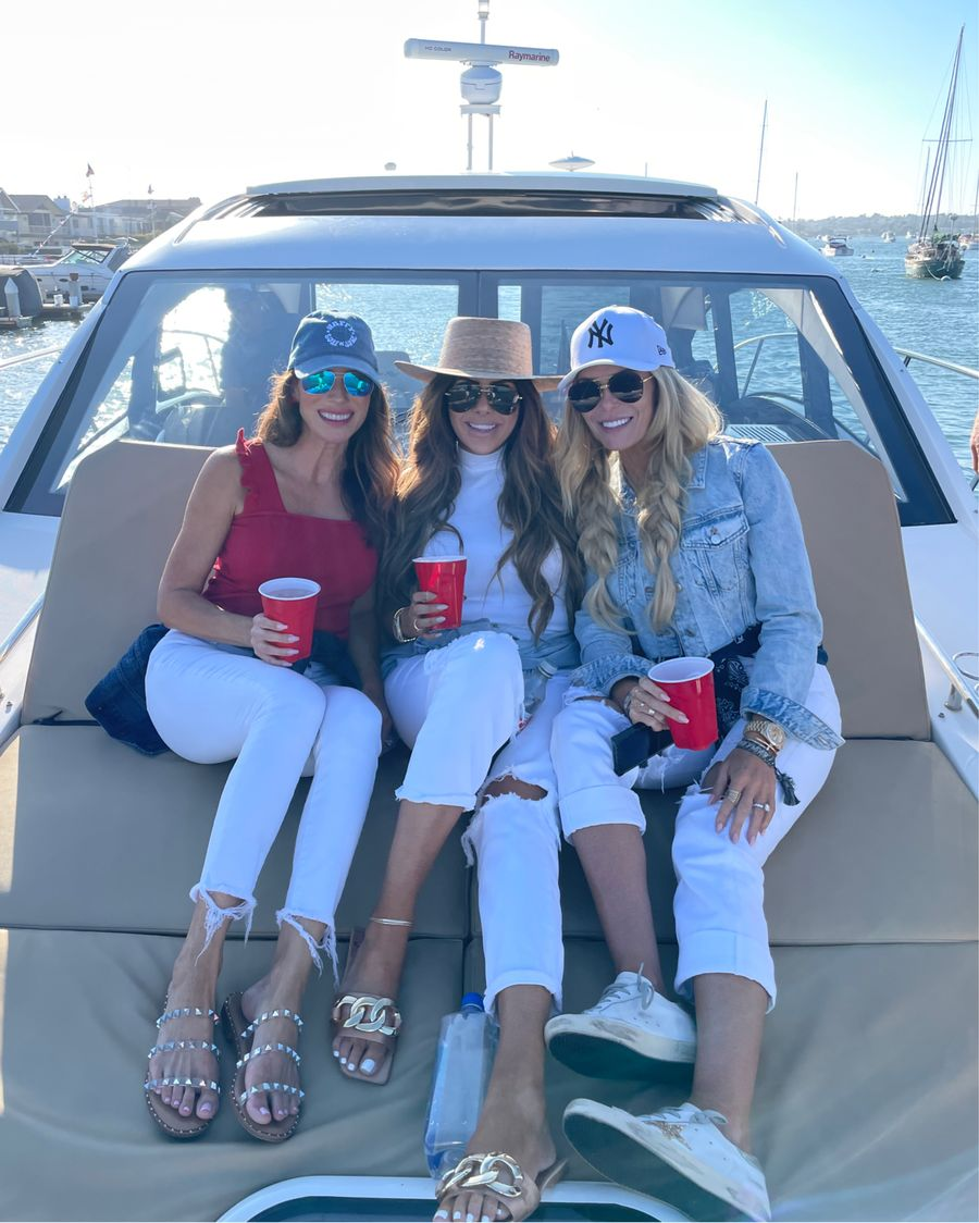 4th of July Outfits, White Denim, Best Sandals Summer 2021, Red White and Blue Outfit, What to Wear in Newport Beach, Boat Outfits, Emily Ann Gemma   Instagram Recap by popular US life and style blog, The Sweetest Thing: image of Emily Gemma sitting with two of her girlfriends on a boat and wearing a white mock neck shirt, Lack of Color boater hat, white distressed jeans, and tan and gold chain strap slide sandals.