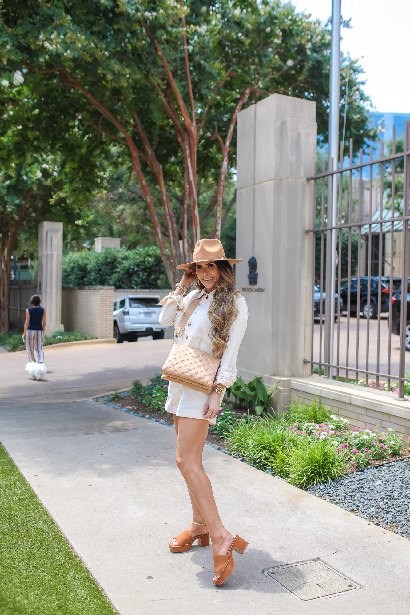 louis vuitton Coussin PM tan 2021, giani bini shoes dillards, emily gemma, ritz carlton dallas, fall outfit idea 2021 pinterest, dallas fashion blogger   Fall Outfit by popular US fashion blog, The Sweetest Thing: image of Emily Gemma waring a Gianni Bini romper, Gianni Bini brown suede mules, tan felt rancher hat, silver anklet, tan Louis Vuitton crossbody bag, and large hoop earrings while standing outside on a sidewalk.