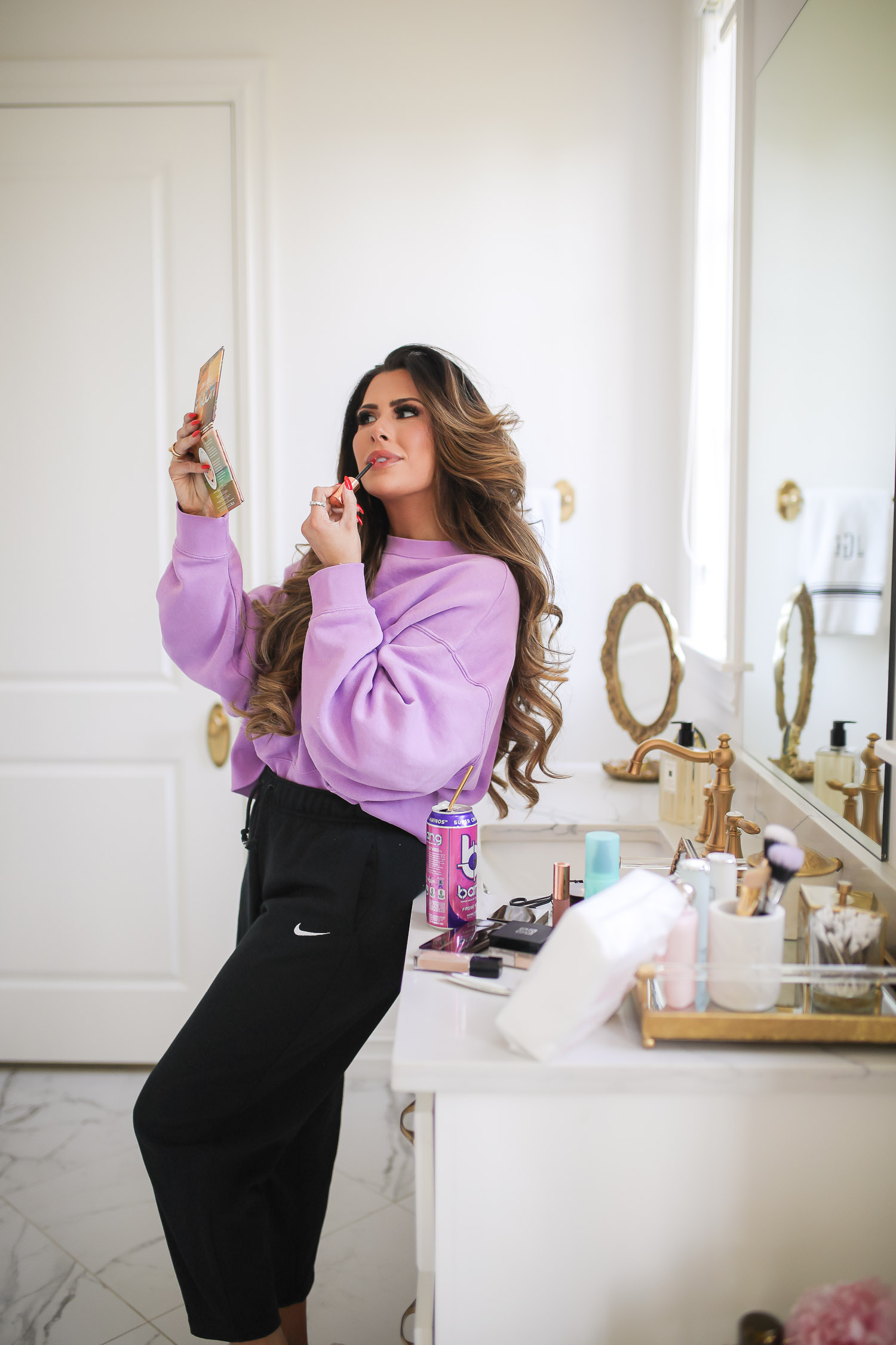 nordstrom beauty must haves fall 2021, sisley pore minimizer review, sisley blur powder review, sisley hyaluronic acid, emily gemma beauty must haves, hoola bronzer palette | Beauty Favorites by popular US beauty blog, The Sweetest Thing: image of Emily Gemma wearing a purple sweatshirt and black Nike jogger pants while leaning against her bathroom vanity and applying lipgloss while she looks in a handheld mirror.