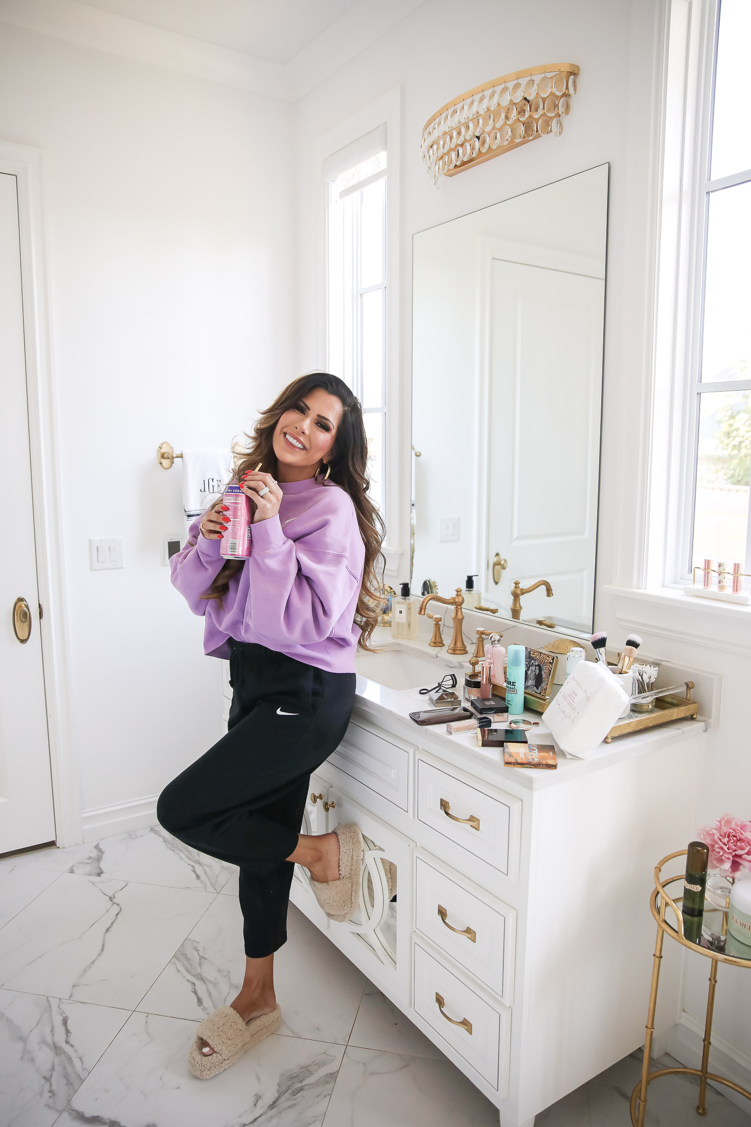 nordstrom beauty must haves fall 2021, sisley pore minimizer review, sisley blur powder review, sisley hyaluronic acid, emily gemma beauty must haves, hoola bronzer palette | Beauty Favorites by popular US beauty blog, Haute Beauty Guide: image of Emily Gemma wearing a purple sweatshirt and black Nike jogger pants while leaning against her bathroom vanity and holding a can of soda in her hands.
