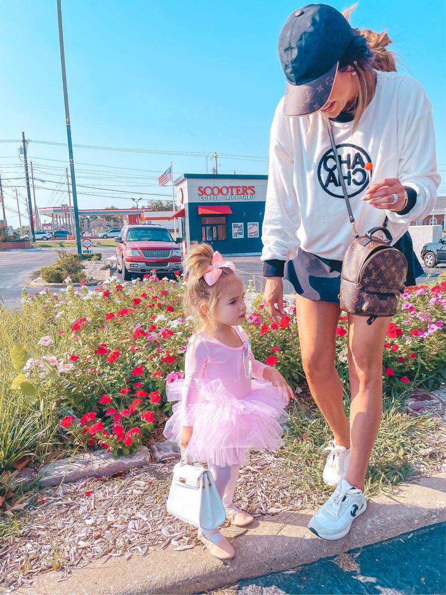 Emily Gemma, Cha Cha Sweatshirt, Cute graphic sweatshirt, athletic skort, Louis Vuitton cap, Louis Vuitton backpack, Chanel sneakers, Fall Transitional outfit ideas