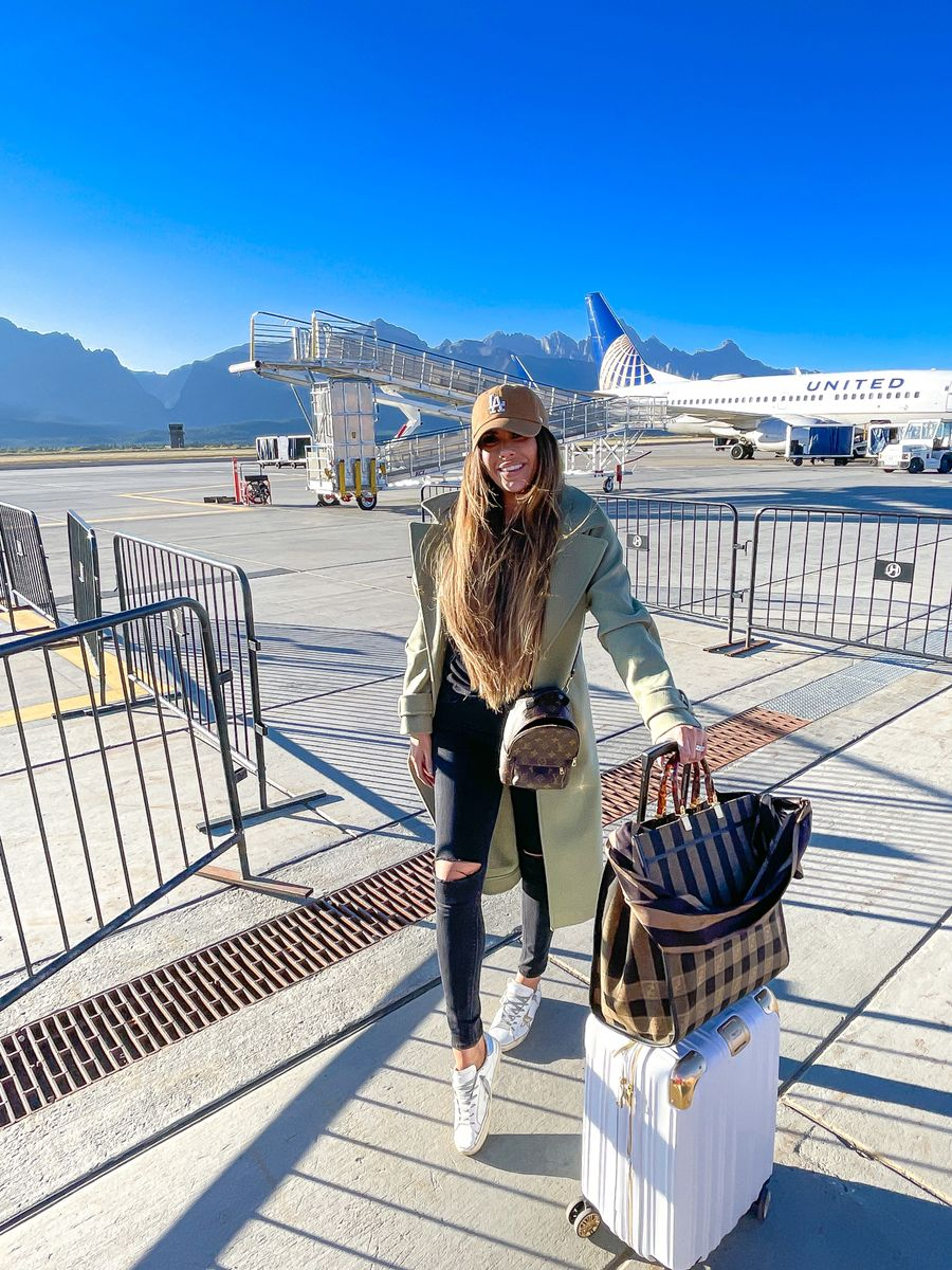 Emily Gemma Travel Style, Airport Outfit, Luggage, Gold and White Suitcases, Fendi Tote Bag, LA Ballcap, Green Coat, Affordable coat, Balmain, Golden Goose, Black Skinny Jeans, Emily Ann Gemma, Fall Outfit, Fall Fashion