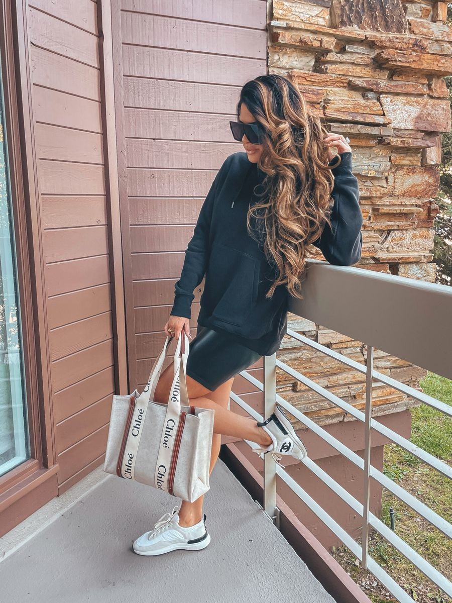 Fall transitional outfit ideas, faux leather biker shorts, black hooded sweatshirt, Chloe tote bag, Chanel sneakers, casual outfit ideas, casual outfit, hiking outfit, oversized sunglasses, Emily Ann Gemma