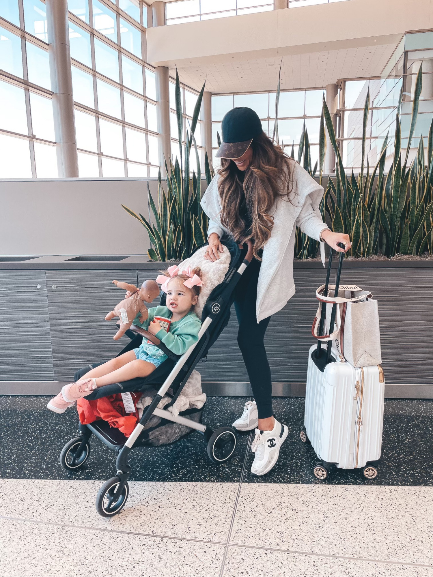 Emily Ann Gemma, Travel outfit, airport outfit, white and gold suitcase, Lululemon leggings, Chanel sneakers, casual outfit, hiking outfit